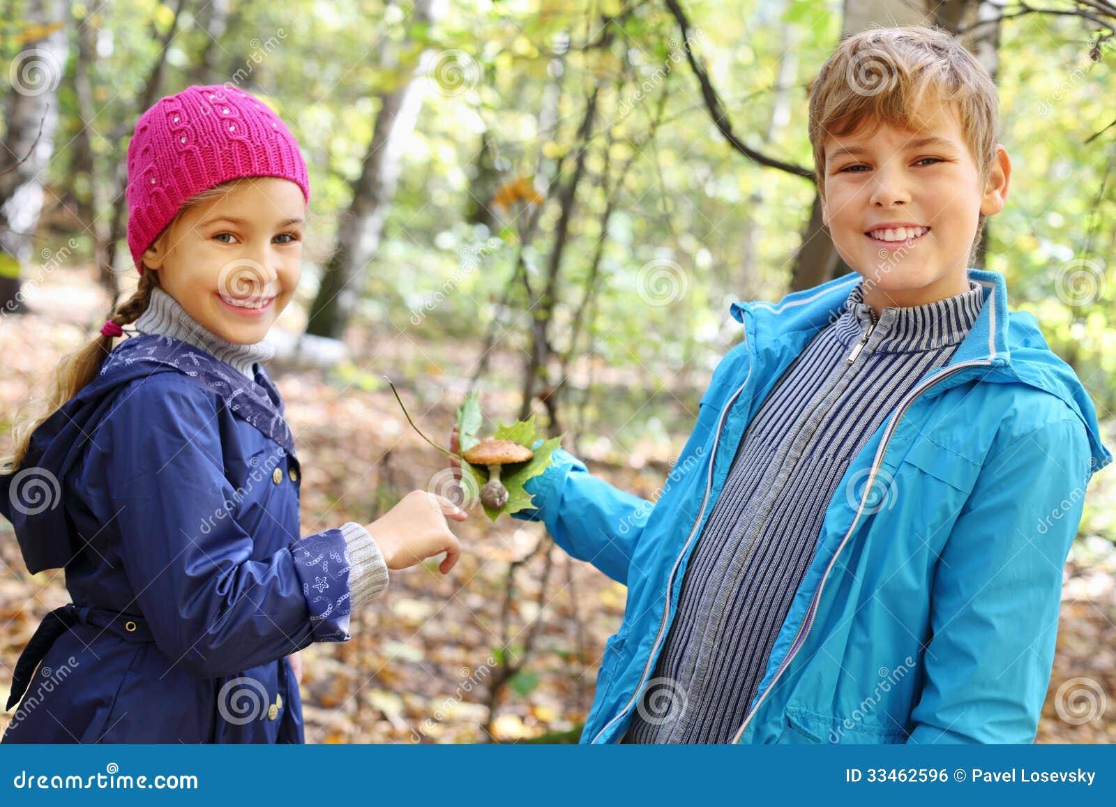 男孩在秋天的举行绿色叶子和女孩微笑