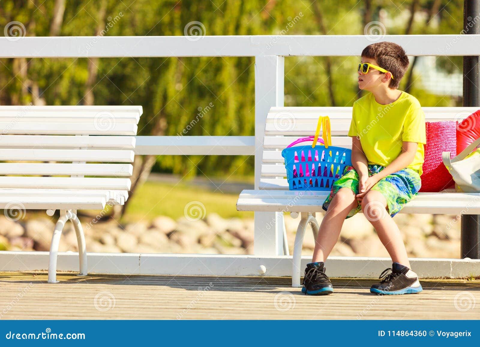 男孩坐与玩具的长凳