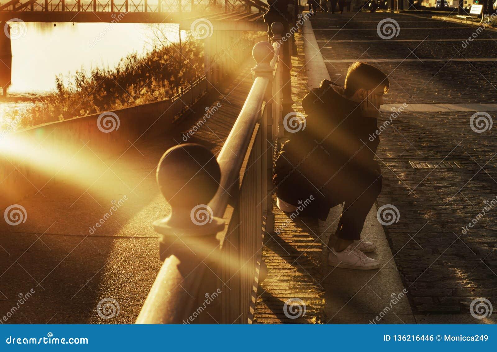 男孩坐城市地板在与光束的日落