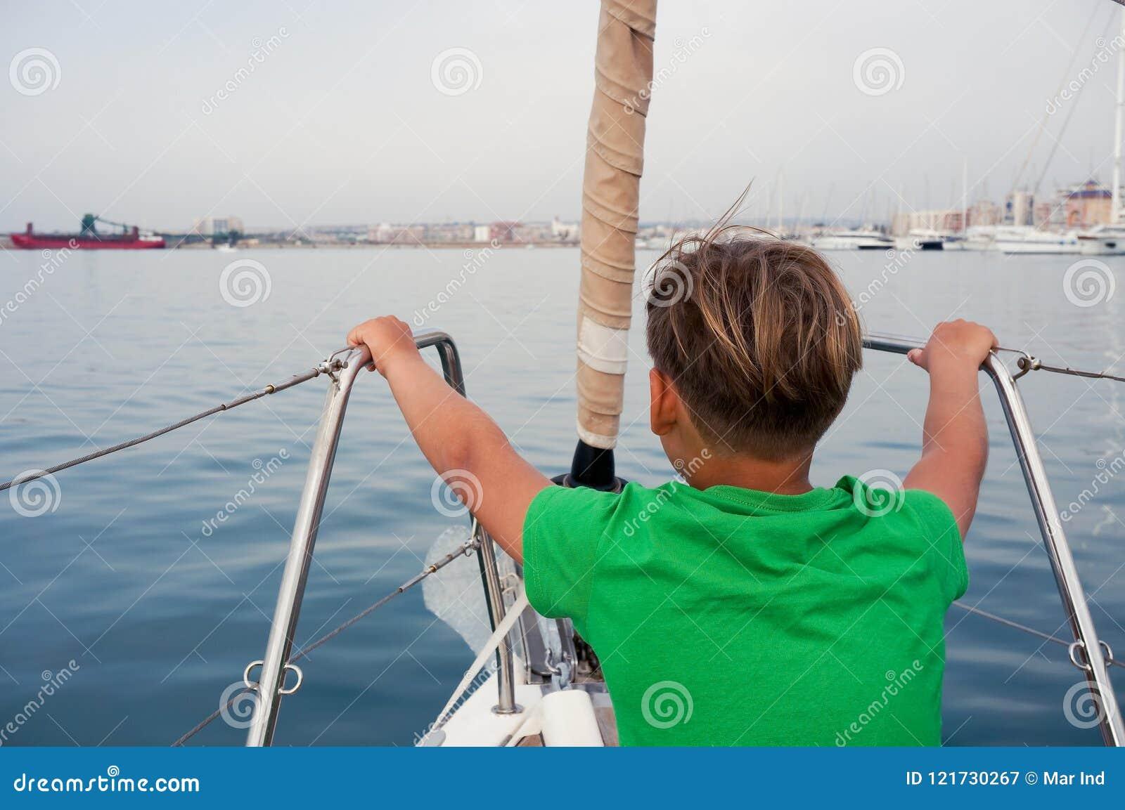 男孩坐游艇鼻子