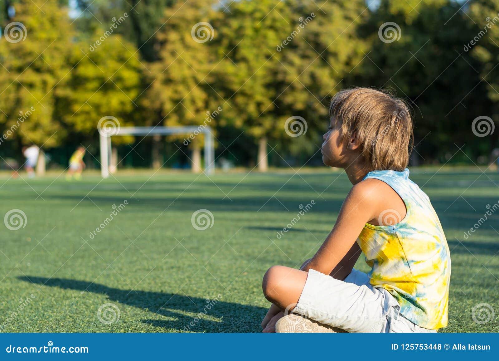 男孩坐草在体育场和手表的边缘