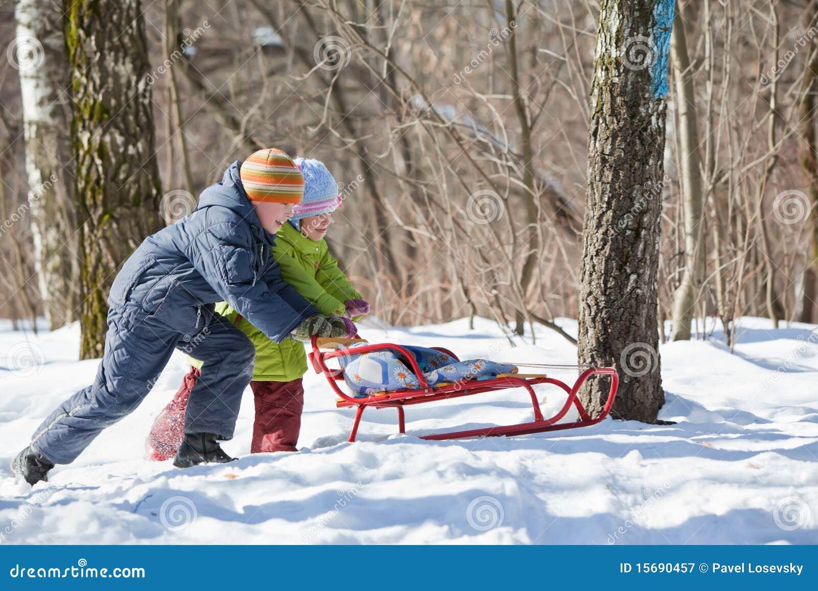 男孩女孩推进爬犁冬天木头