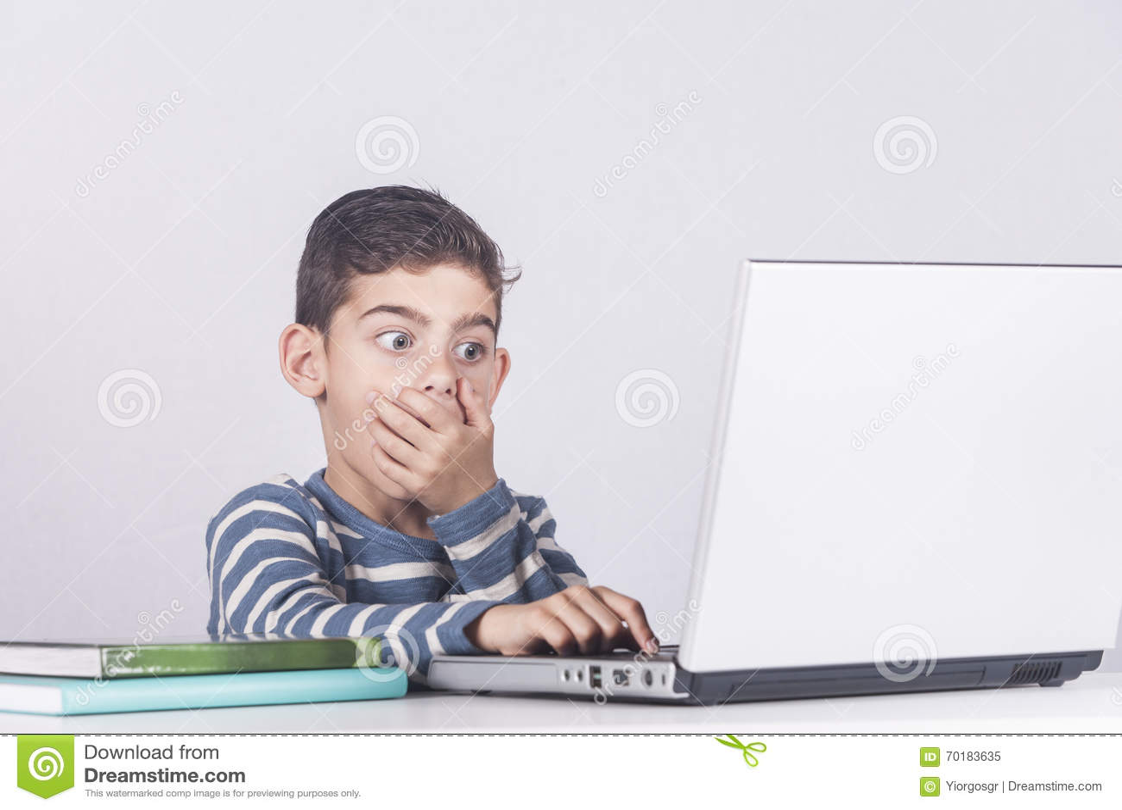 年轻男孩起反应,当使用膝上型计算机时