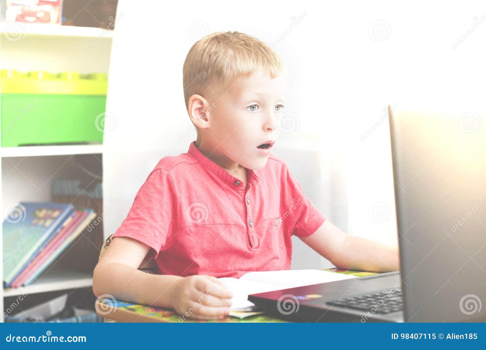 男孩起反应,当使用膝上型计算机时