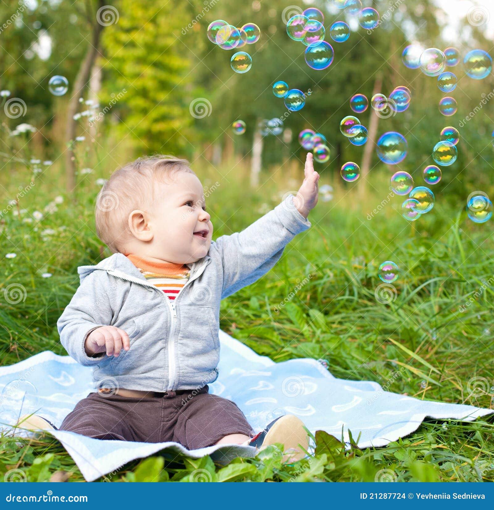男孩起泡演奏坐的肥皂的草