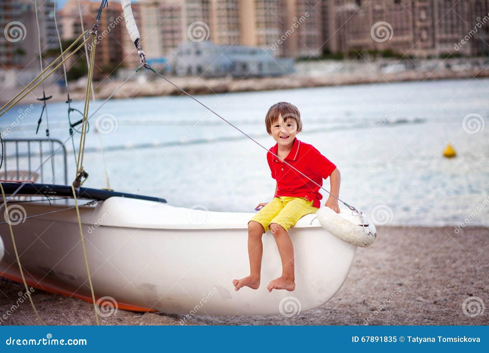 男孩,使用在海滩在雨以后的晚上与玩具