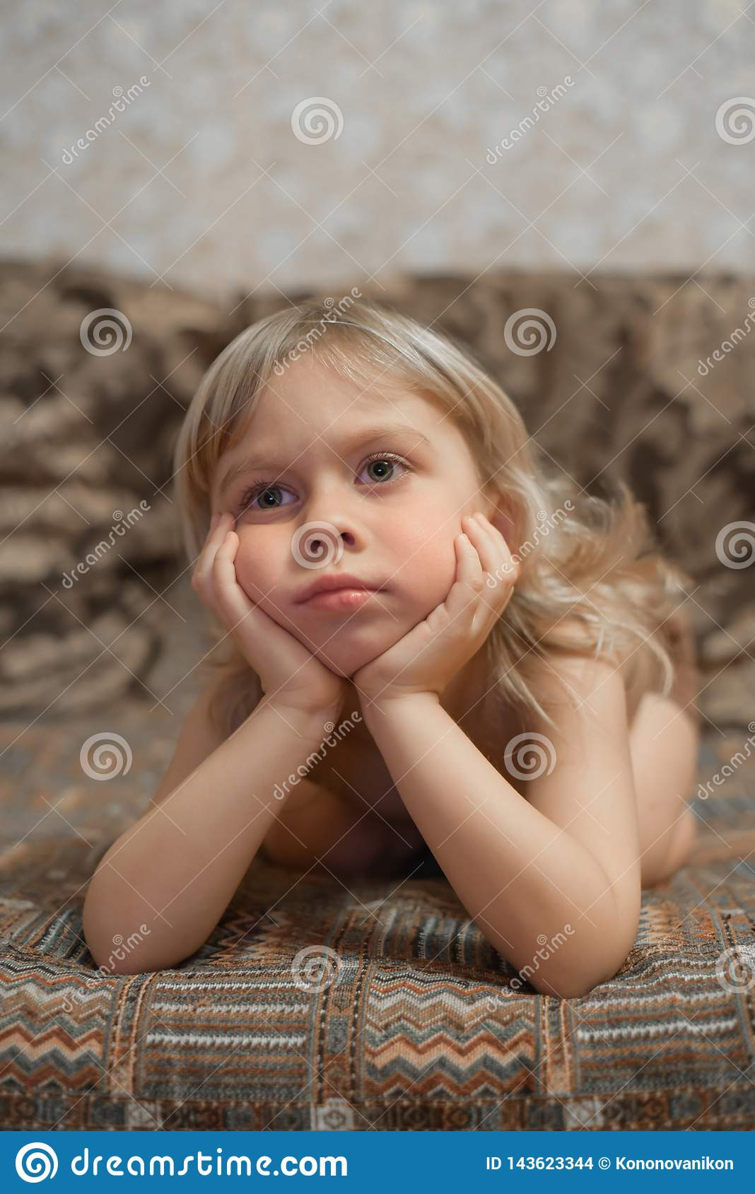 男孩4岁在家在长沙发和看着电视说谎 白肤金发的男孩纵向