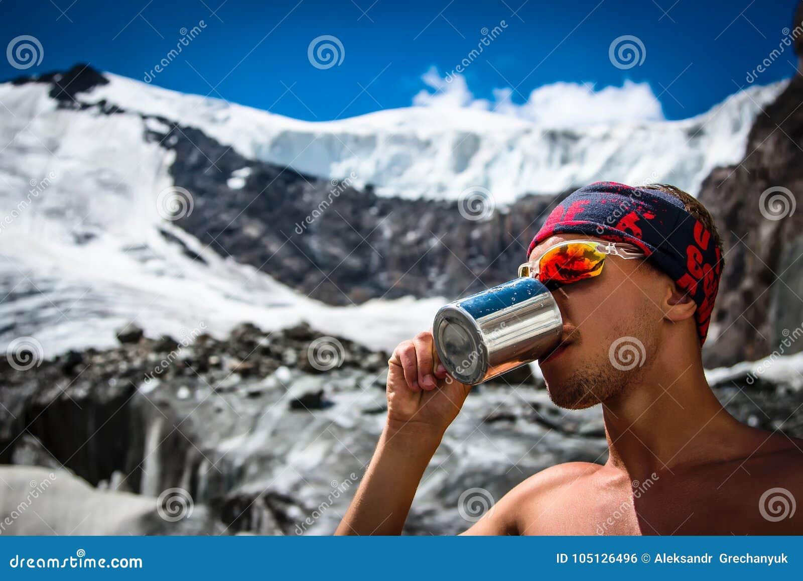 男性从一个杯子的登山家饮用水在山旅行生活方式概念冒险激活假期extre的冰川