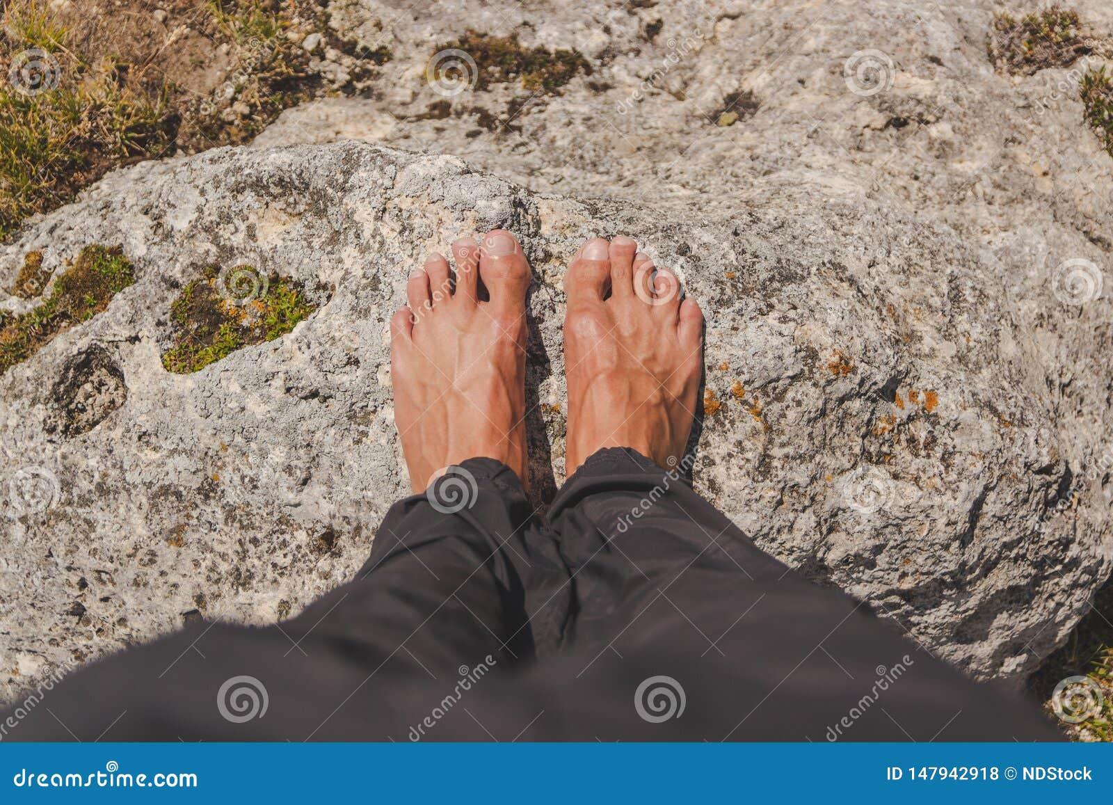 男性在岩石赤足安置了