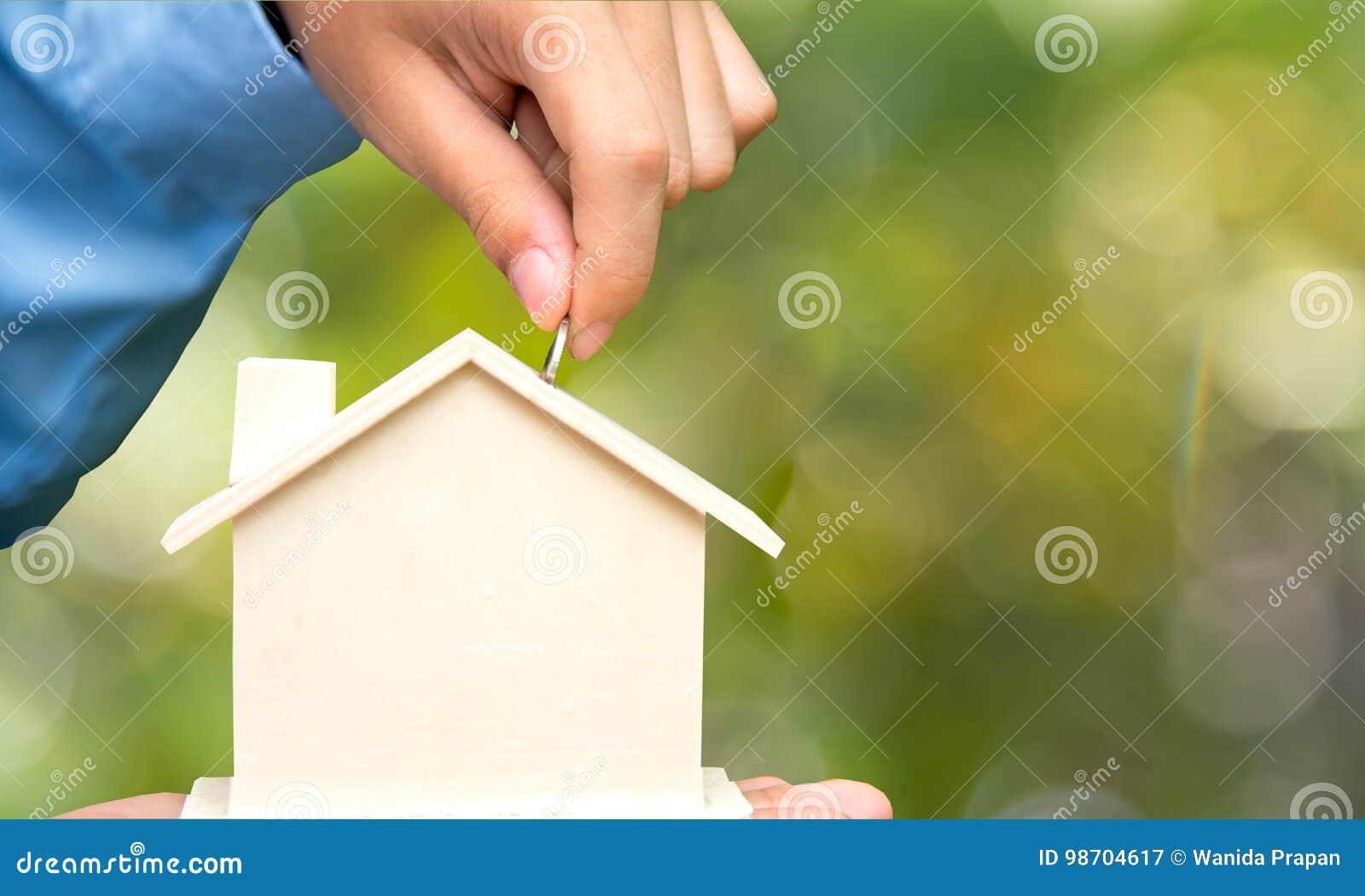 男性手拿着硬币的和贪心房子银行存金钱,绿色自然背景 投资和救球概念