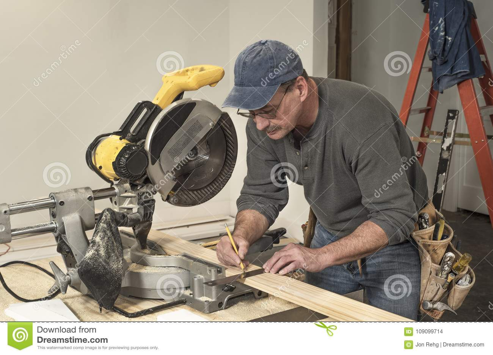 男性木匠佩带的工具传送带和使用方形的工具标记切开的木委员会在专业剁看见了