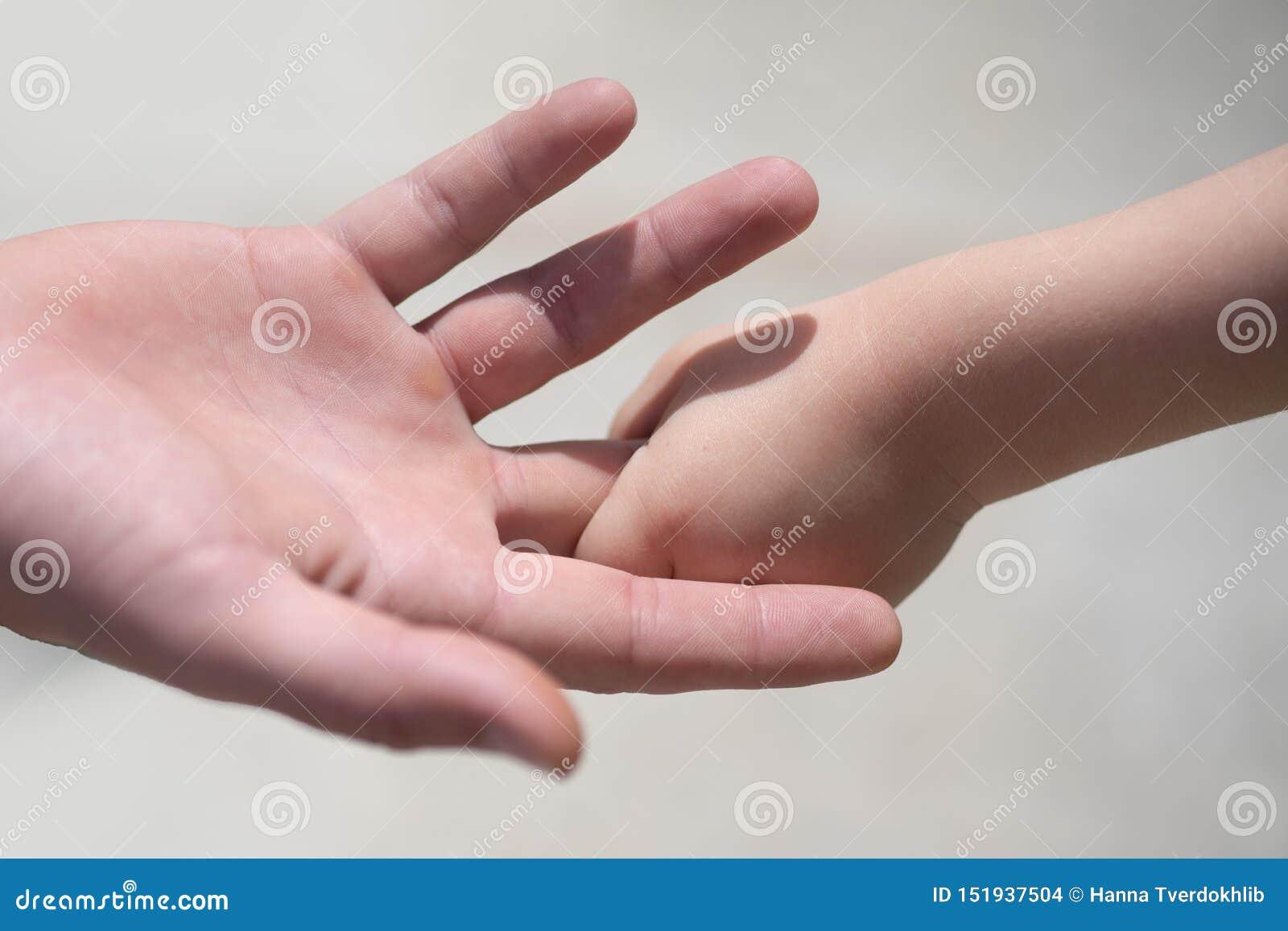 男性父亲的小男婴藏品手指的两只接触的手特写镜头作为家庭爱和信任的标志的