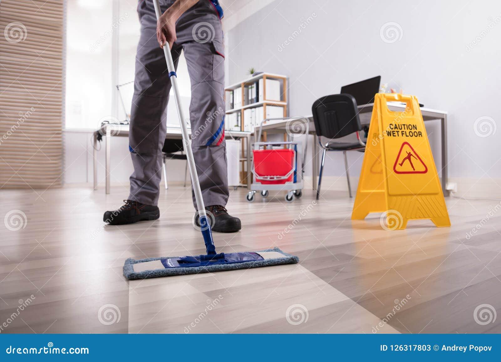 男性管理员清洁地板在办公室