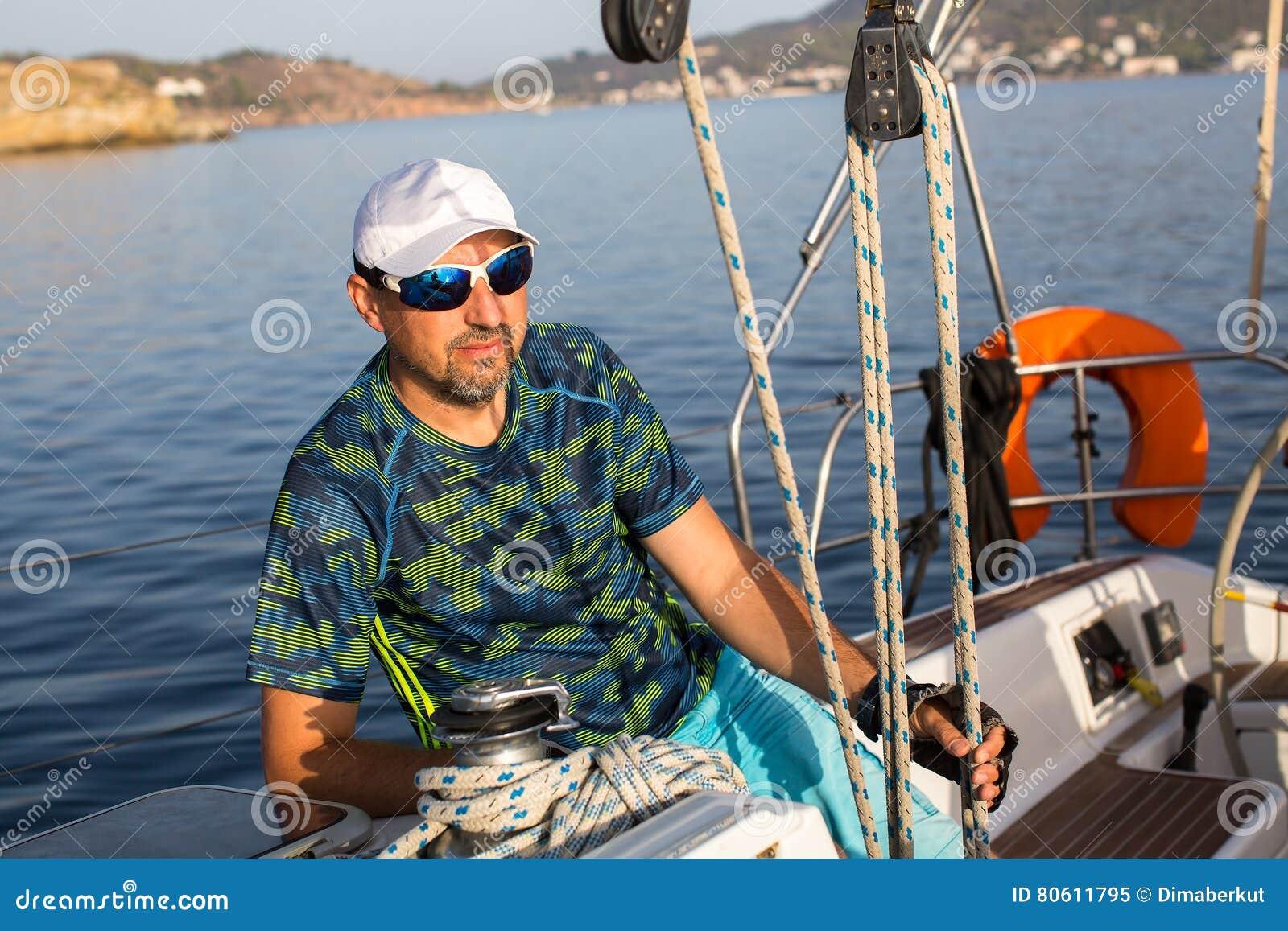 男性船长坐他的航行游艇在索具附近 体育运动