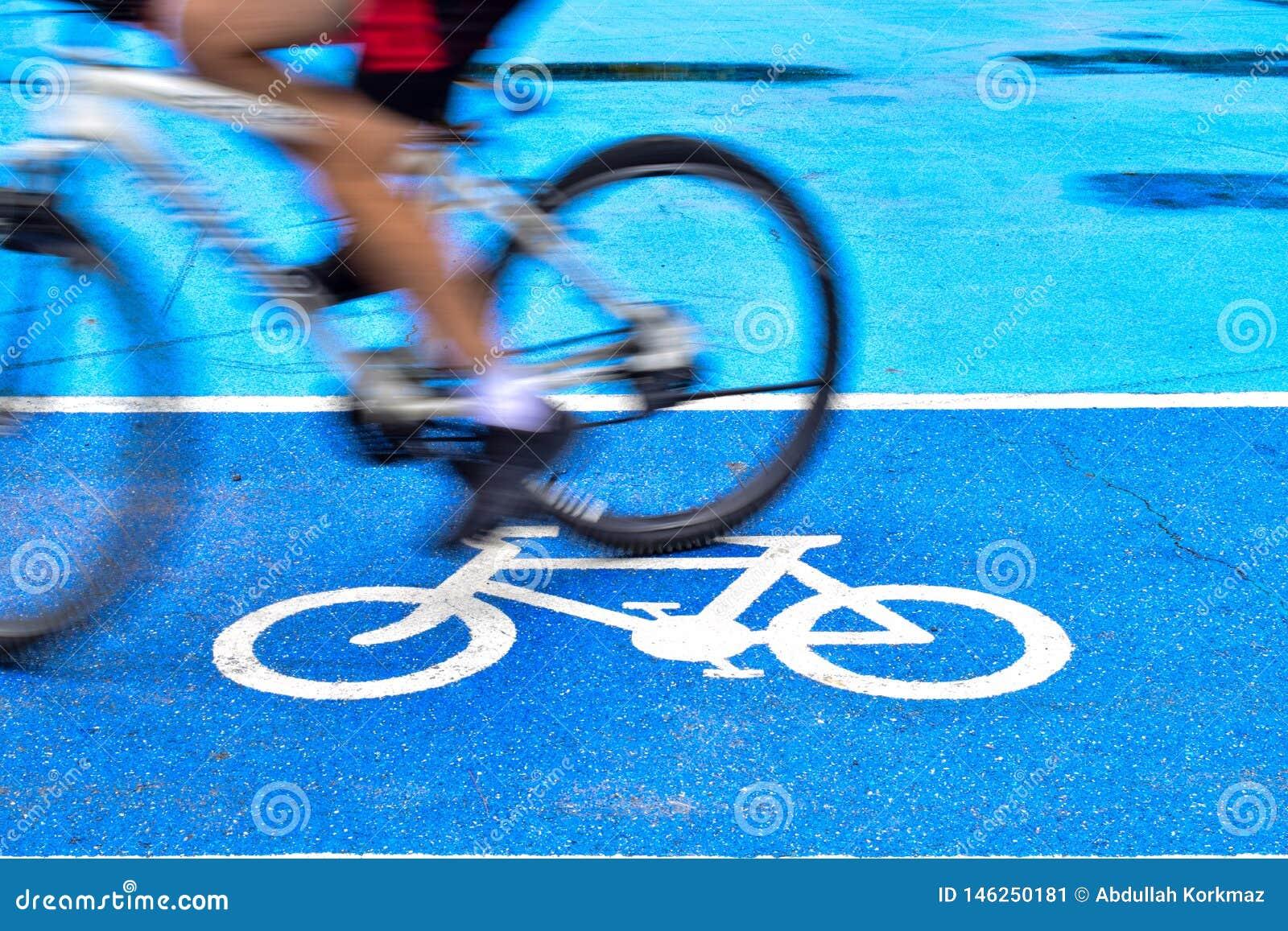 男性骑自行车者在自行车标志车道骑自行车