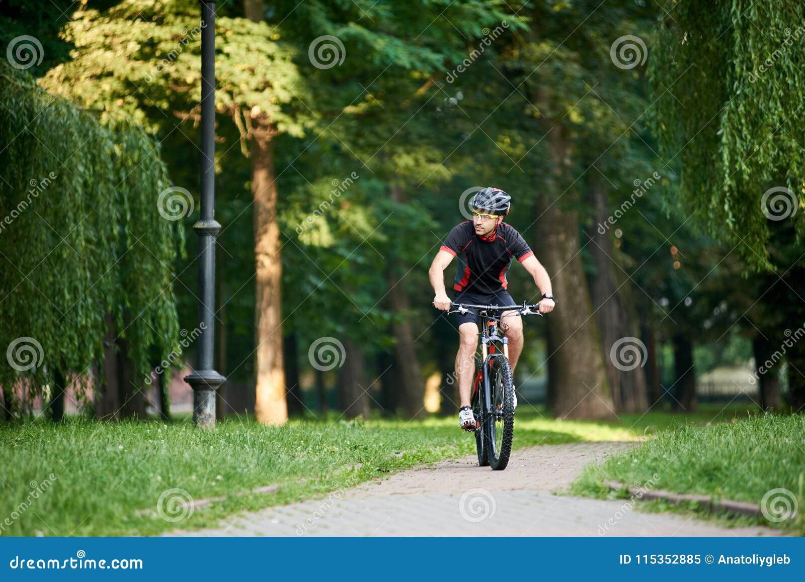 男性骑自行车者训练在绿色公园