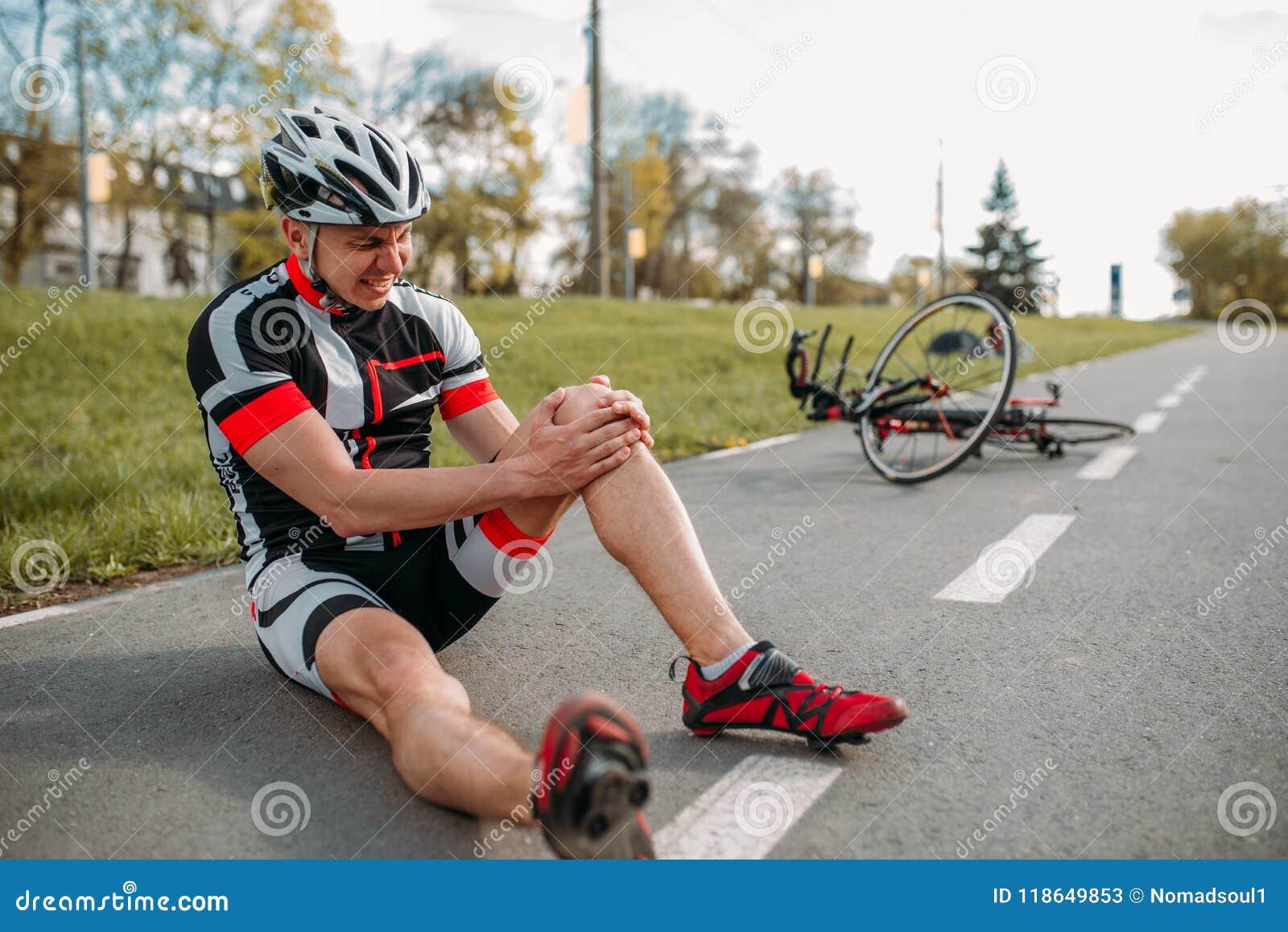 男性bycyclist跌下自行车并且击中了他的膝盖