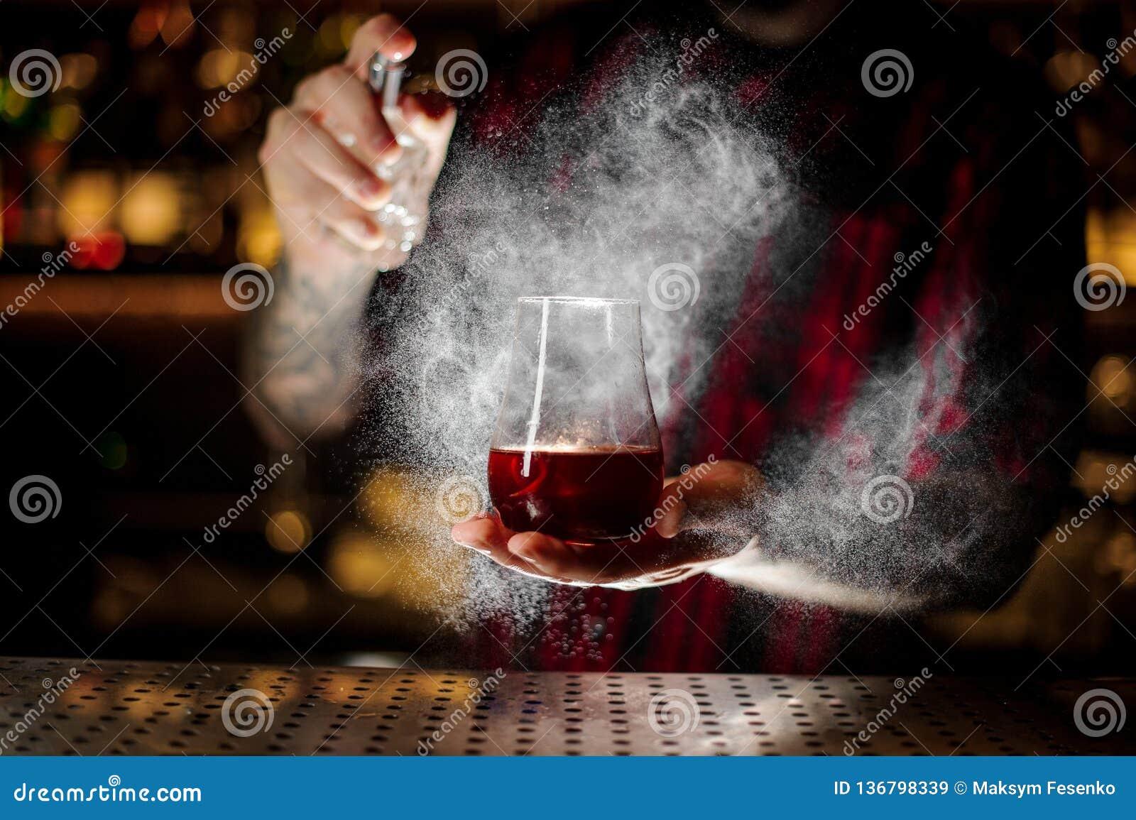 男服务员洒苦涩入玻璃与红色甜鸡尾酒