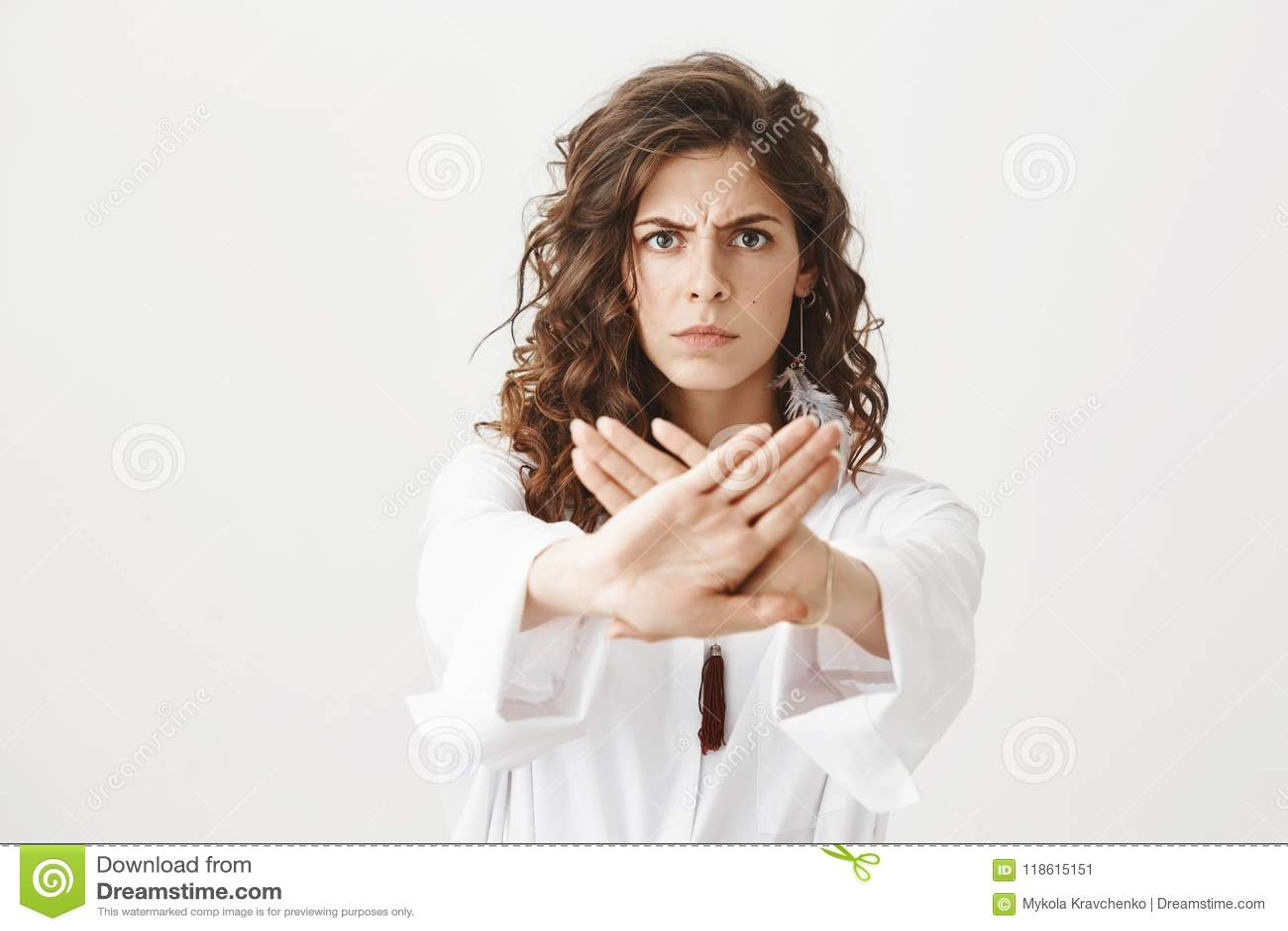画象严肃担心白种人女性皱眉,当伸往照相机的手与中止时打手势,禁止