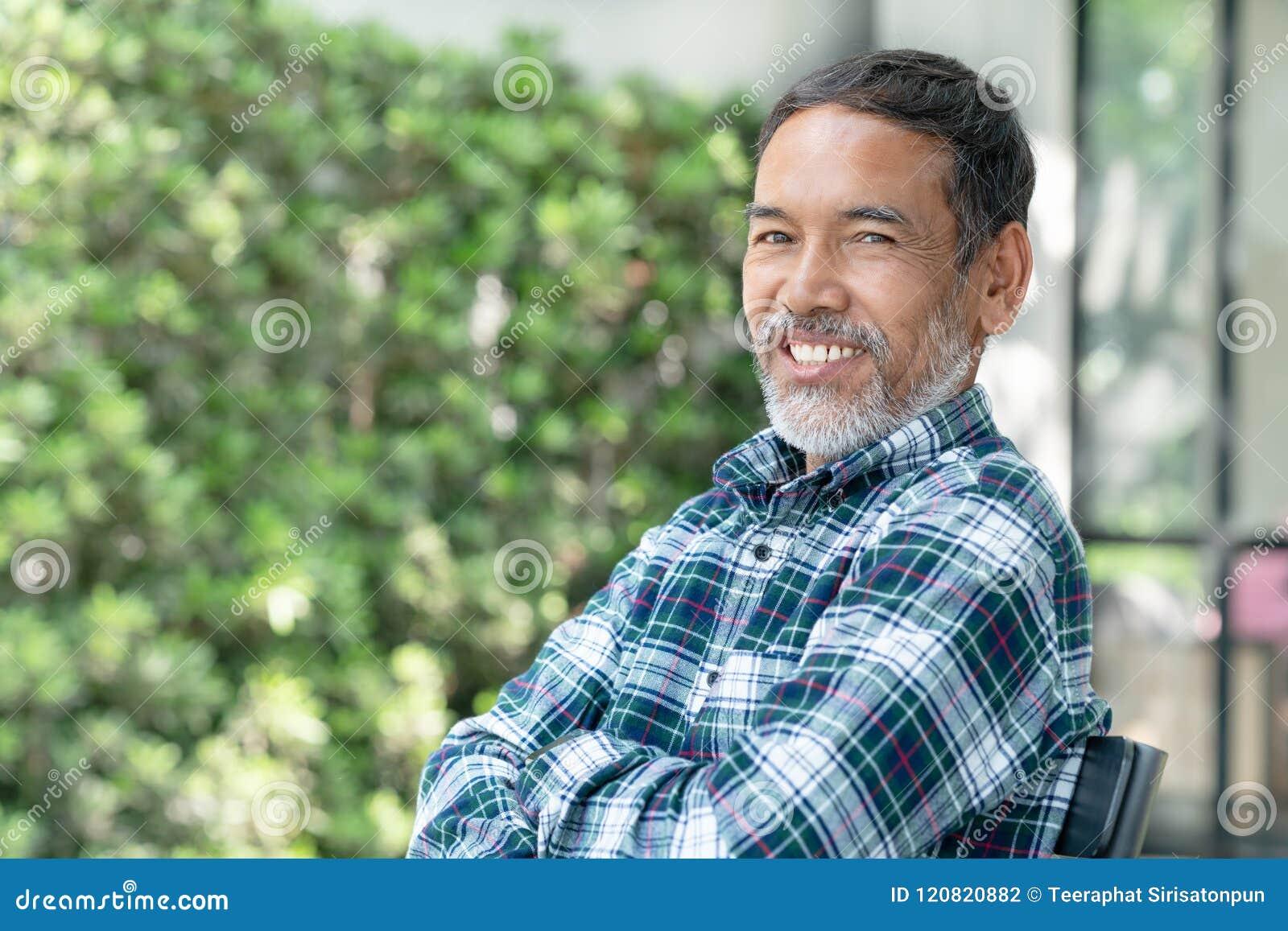 画象微笑的可爱的成熟亚裔人退休了与时髦短胡子坐室外