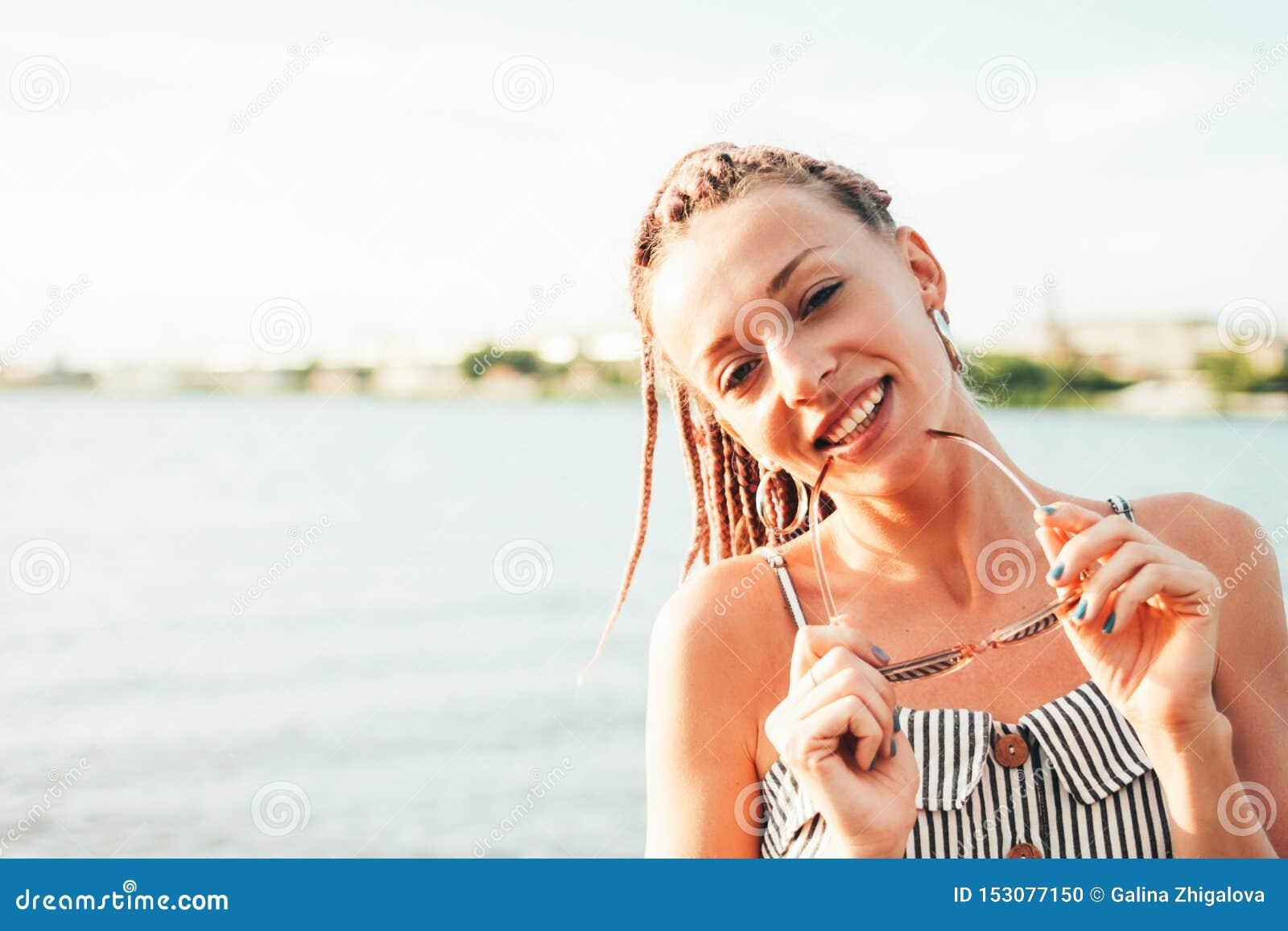 画象愉快的无忧无虑的年轻女人的关闭有在太阳镜的非洲辫子的享有在海滩的生活,暑假时间