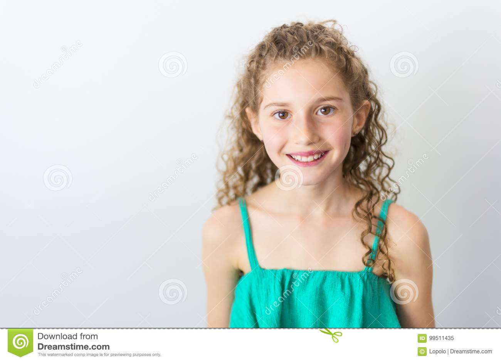画象愉快,微笑,确信的9岁有卷发的女孩,隔绝在灰色