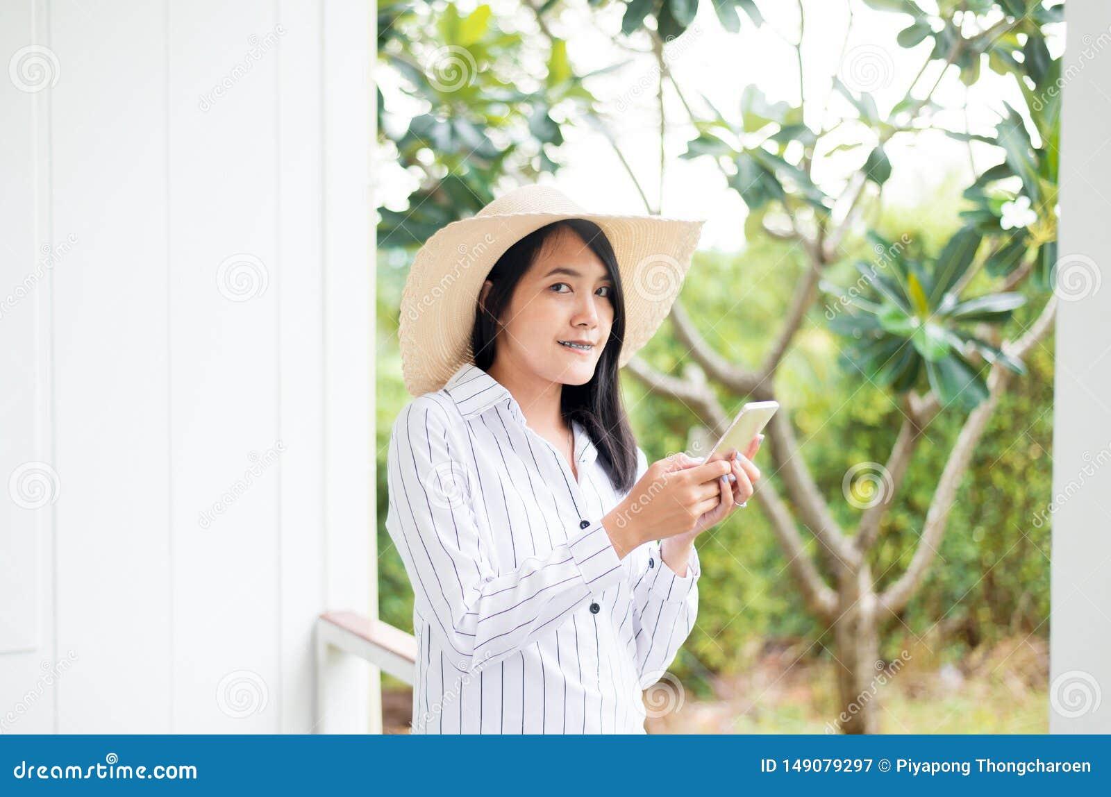 画象美丽的亚洲女性固定的单元电话和微笑对室外,正面认为,好态度