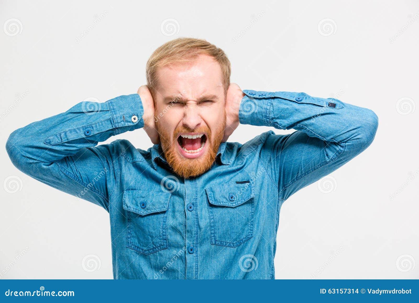 疯狂的歇斯底里的人用人工和尖叫关闭了耳朵