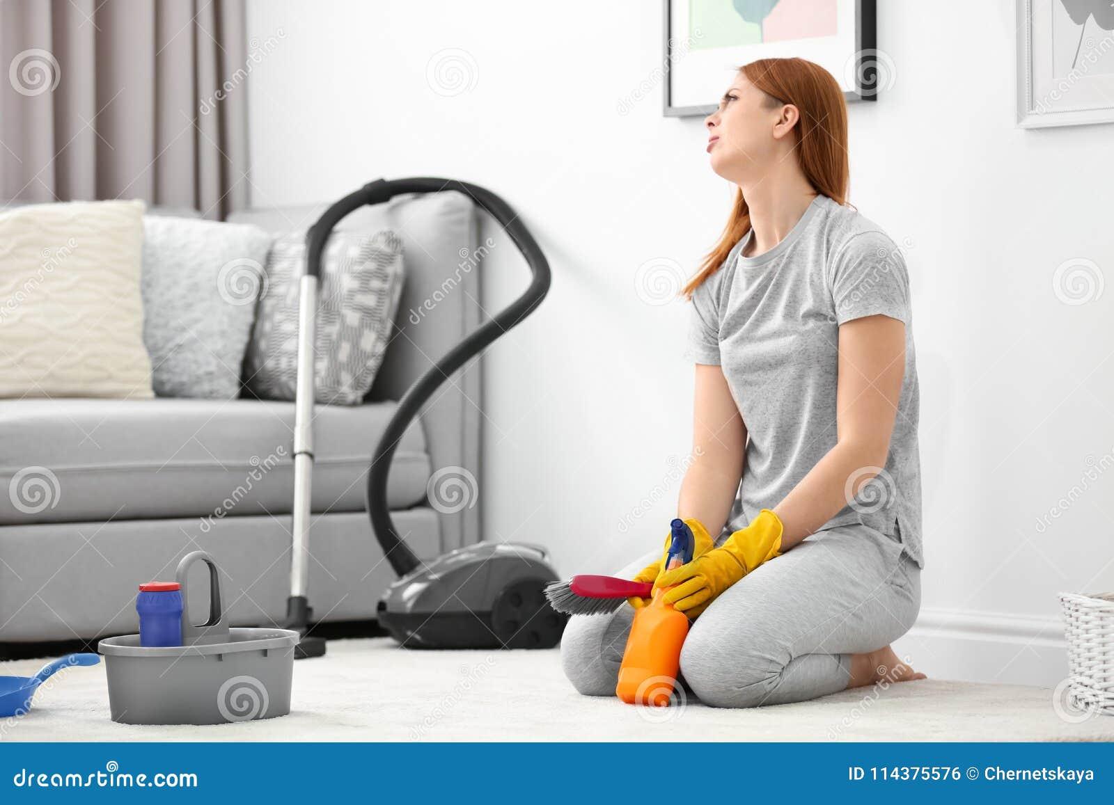疲乏的主妇清洁地毯