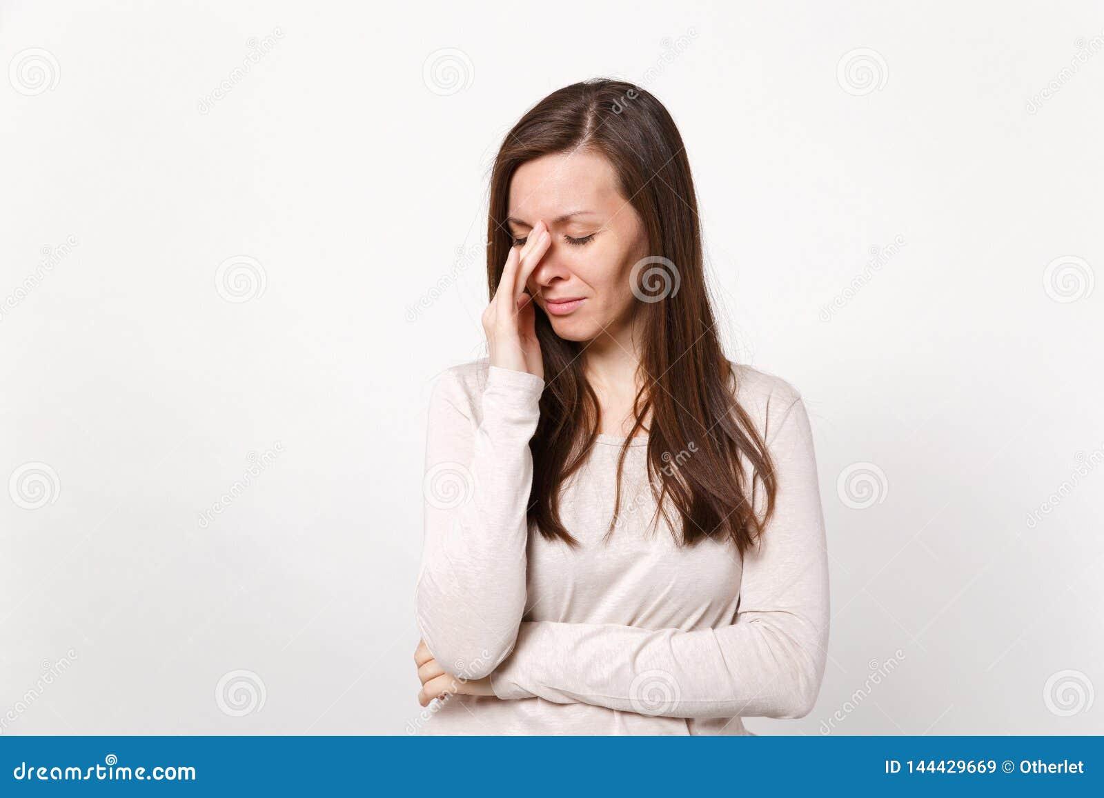疲乏的哭泣的不满意的年轻女人画象擦泪花的轻的衣裳的与在白色墙壁上隔绝的手