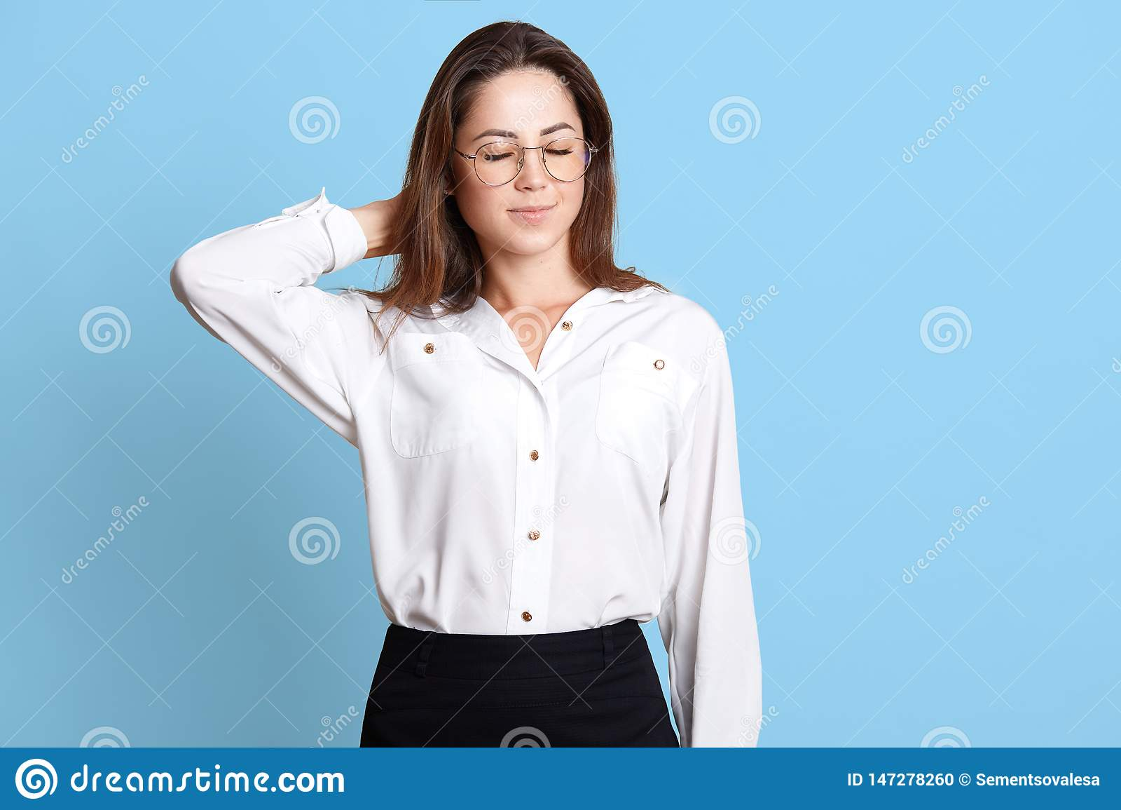 疲乏的女商人,礼服的年轻白种人妇女画象充满脖子痛的按摩她的与闭合的眼睛的脖子,摆在