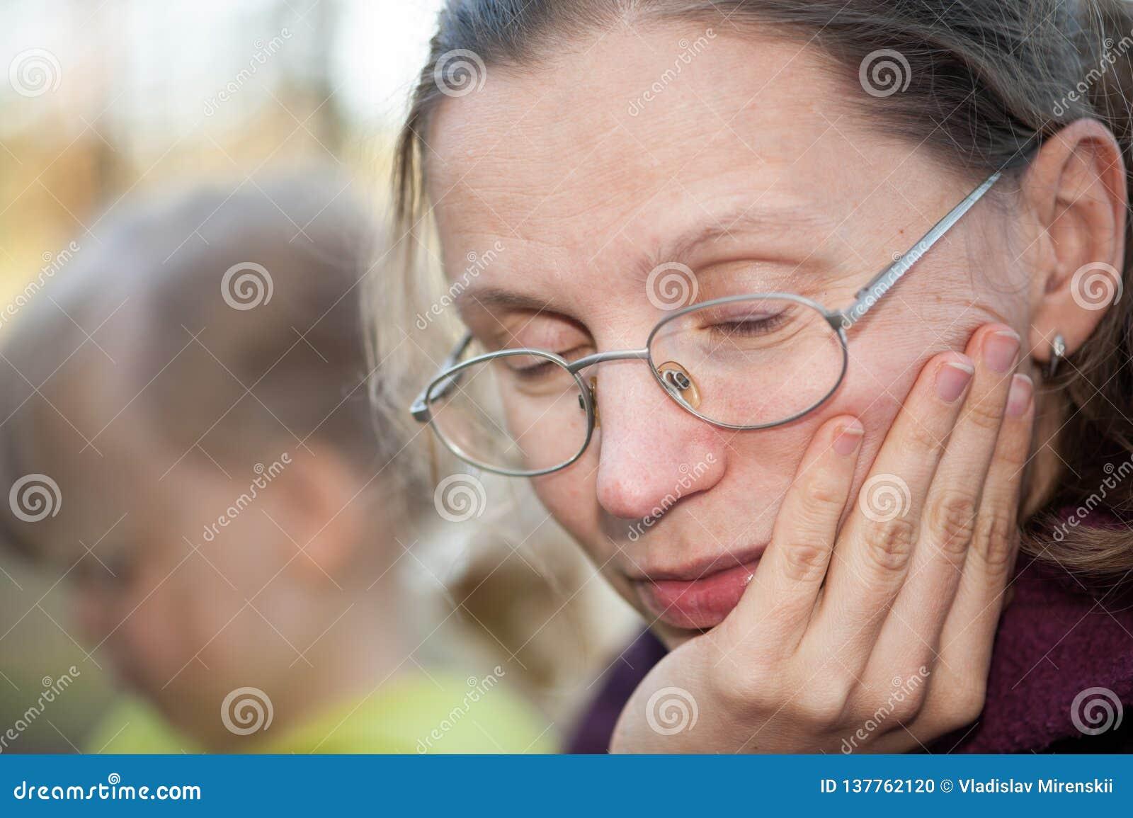 疲乏的母亲打盹的坐在她的女儿旁边