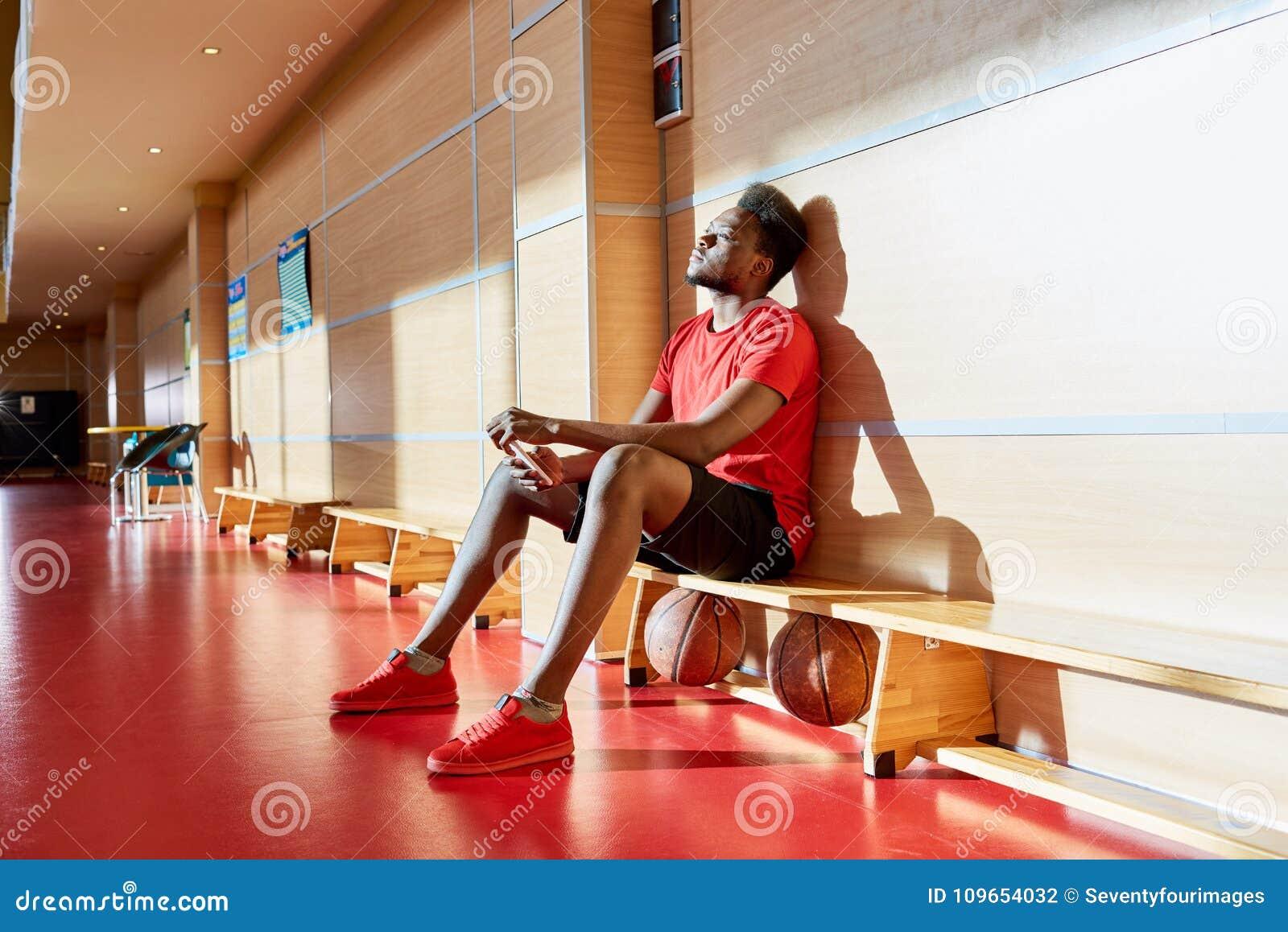 疲乏的美国黑人的蓝球运动员坐边线