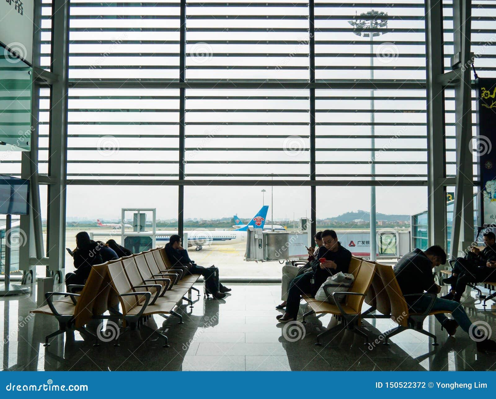 白云队,广州,中国- 2019年3月10日-乘客坐和等待在白云国际机场内的一扇登机门 一架飞机
