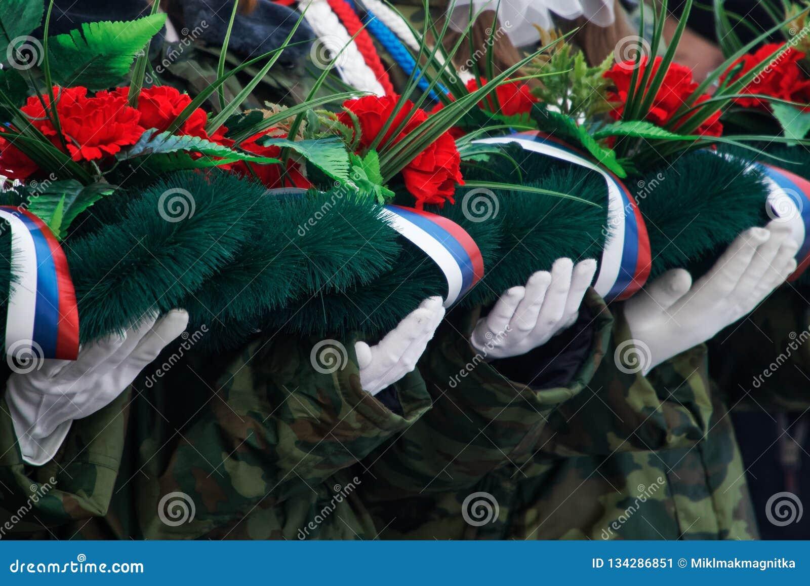 白手套的手拿着一个花圈和花以记念在战争和武力冲突中杀害的那些