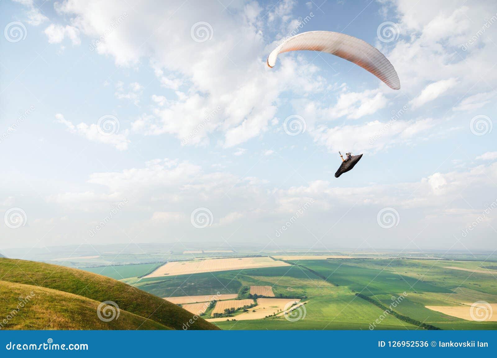 白橙色滑翔伞飞行在山岭地区