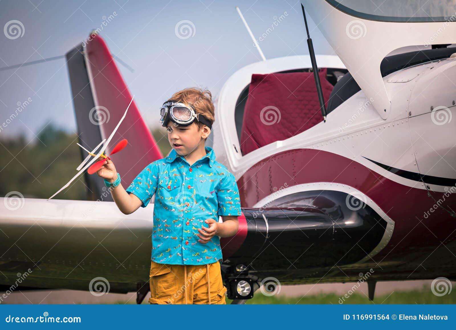 白种人男孩黄色短裤,一件蓝色衬衣的和航空点的对玩具飞机手中和h负