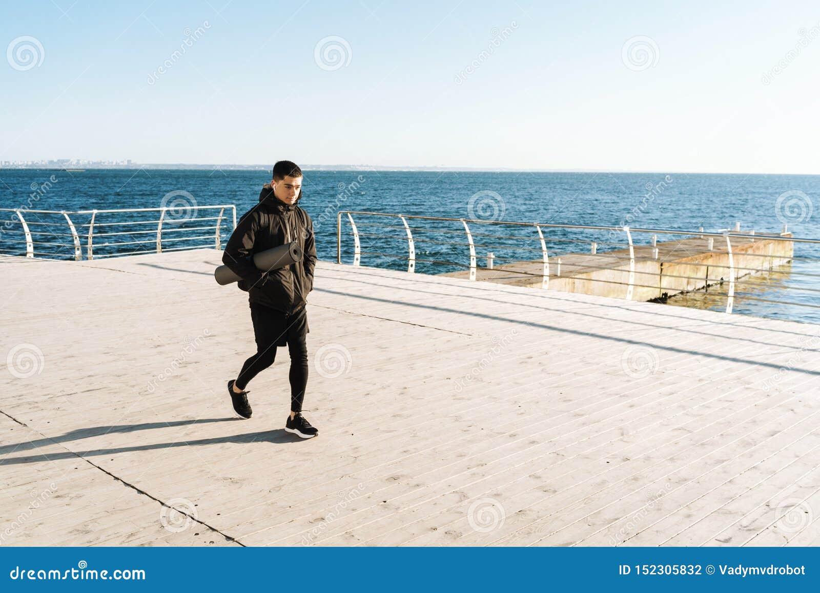 白种人走由海边的运动员佩带的earpods照片在早晨锻炼以后