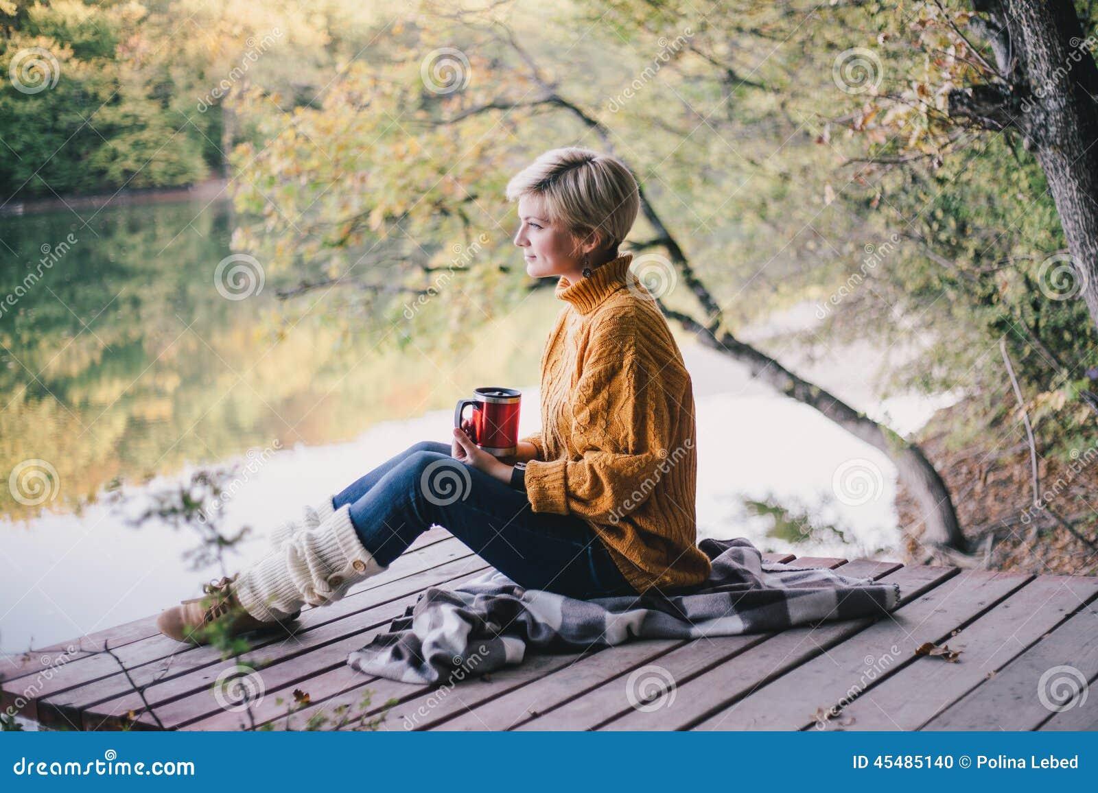 白肤金发与坐在有杯子的湖附近的蓝眼睛热的茶