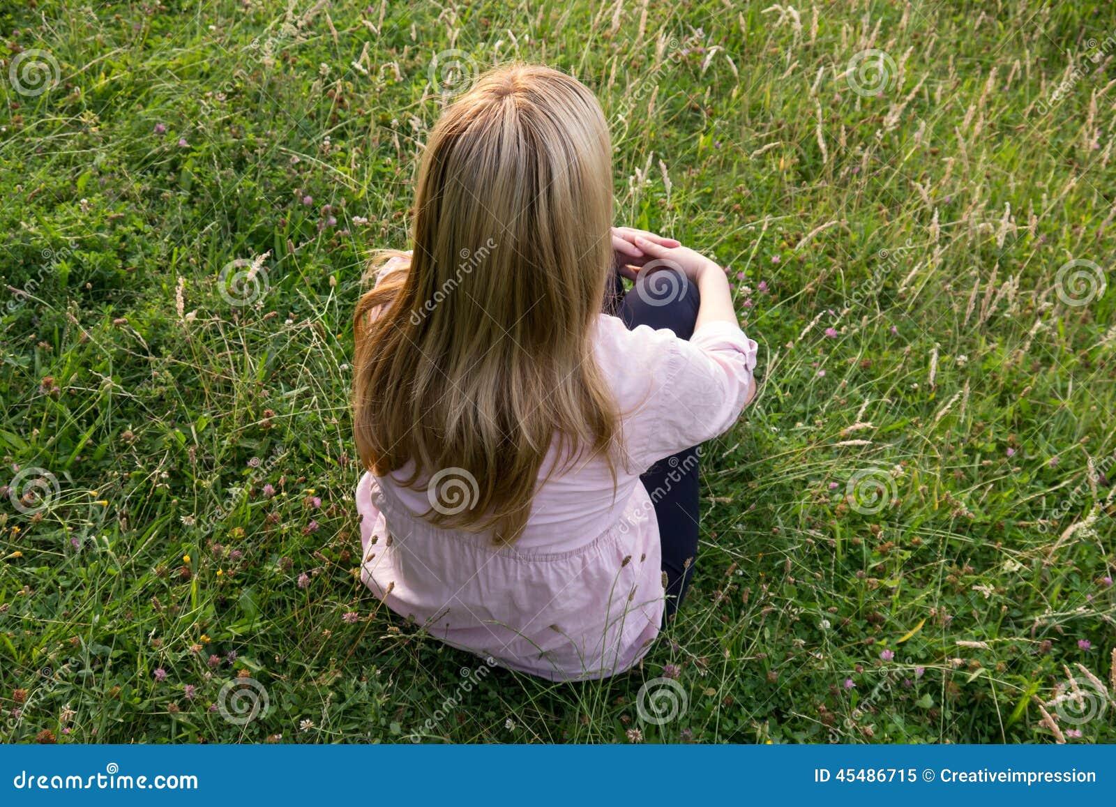 白肤金发的妇女坐草甸