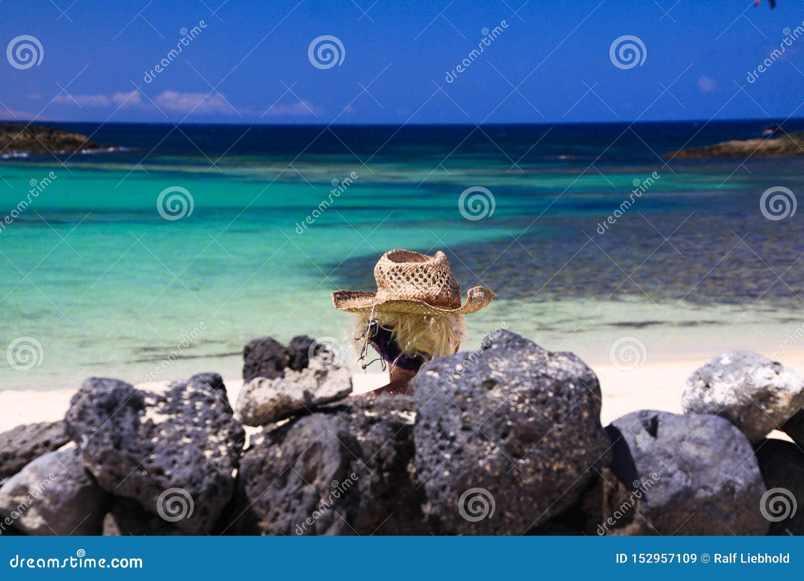 白肤金发的妇女头有草帽的在被堆的自然岩石后墙壁坐与绿松石海洋-费埃特文图拉岛,El的海滩