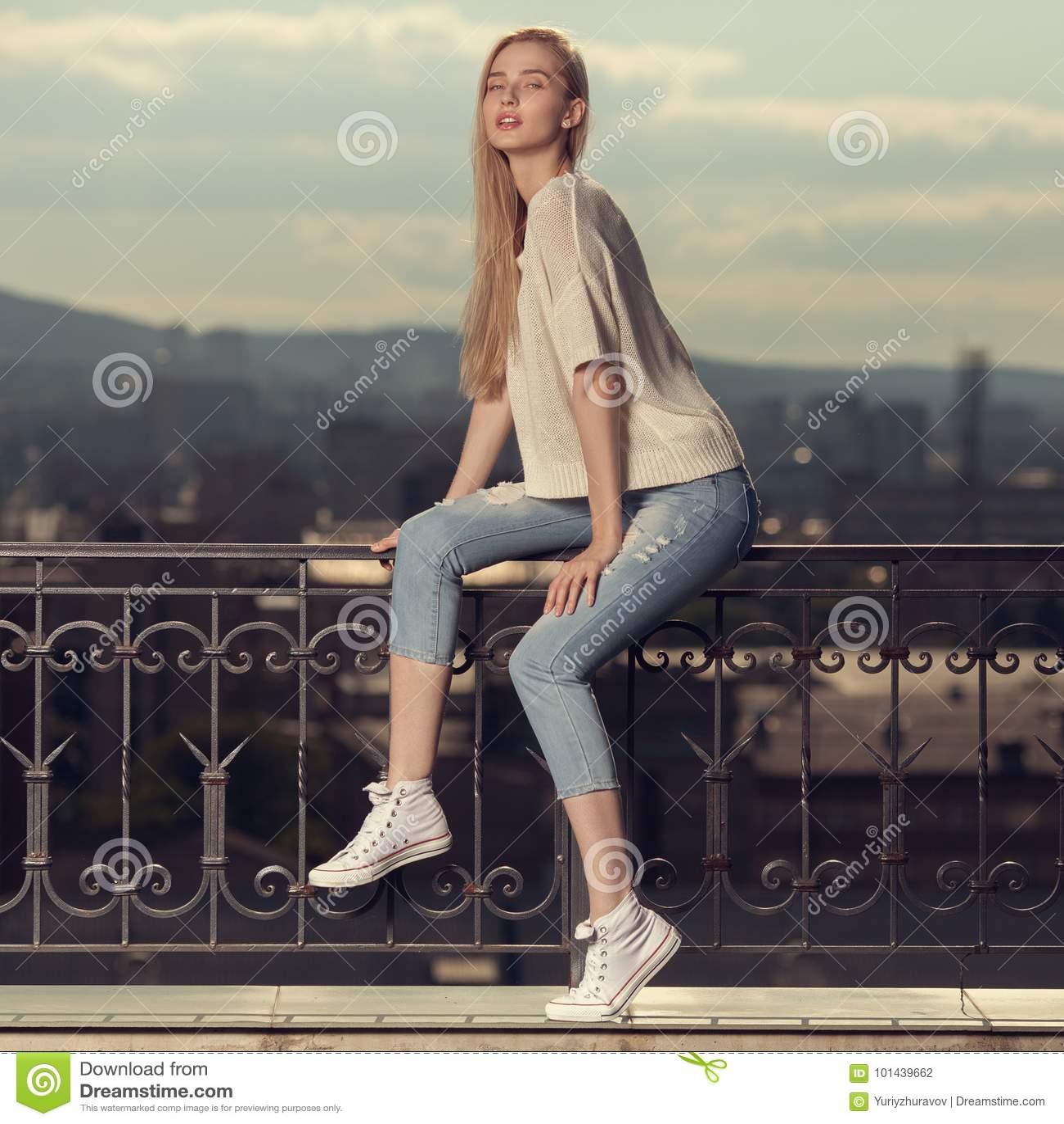 白肤金发的妇女方式纵向 牛仔裤和运动鞋