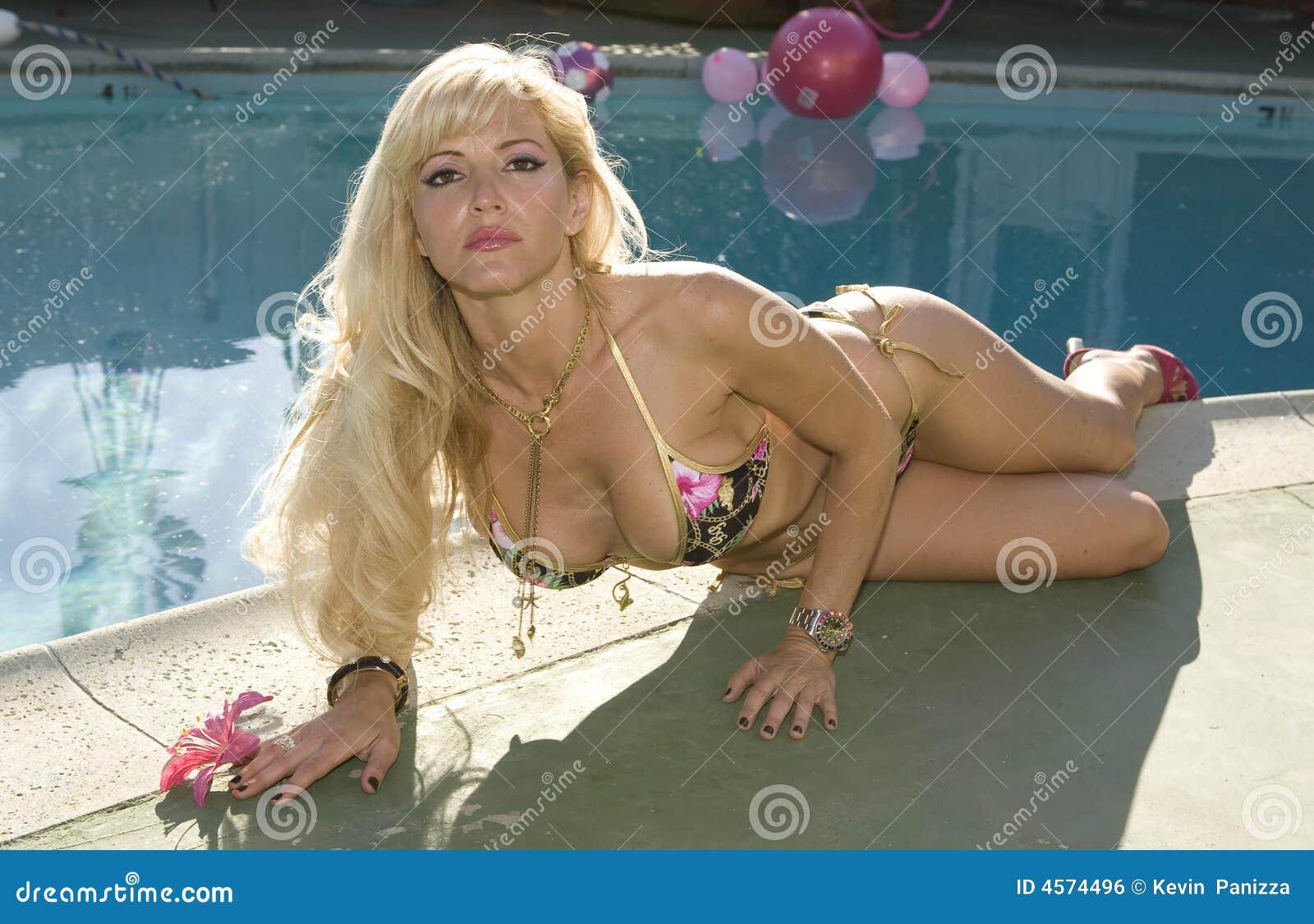 白肤金发的放置的游泳池边妇女