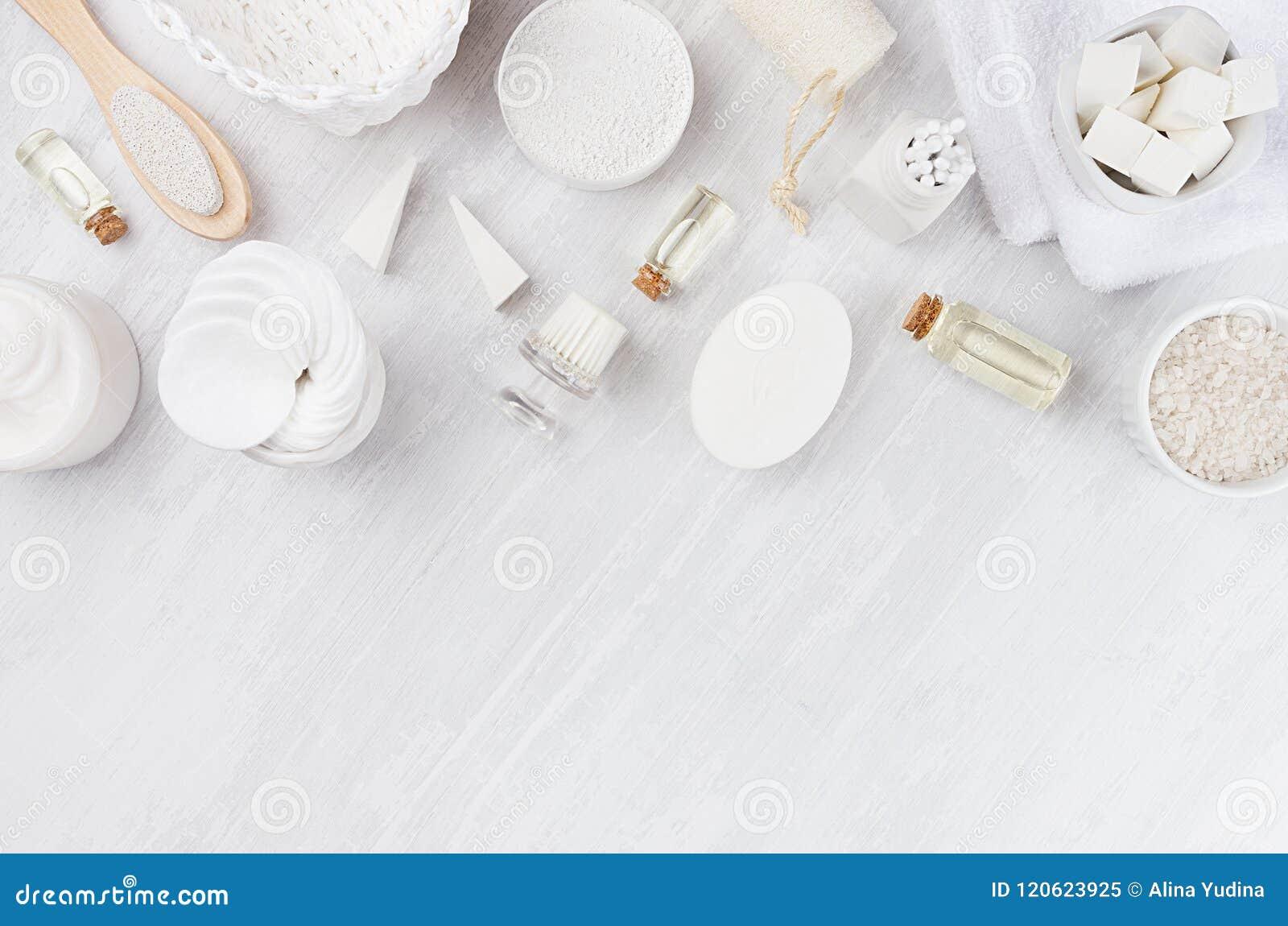 白色化妆用品设置了身体关心和浴辅助部件的自然产品作为在白色木板,顶视图的边界