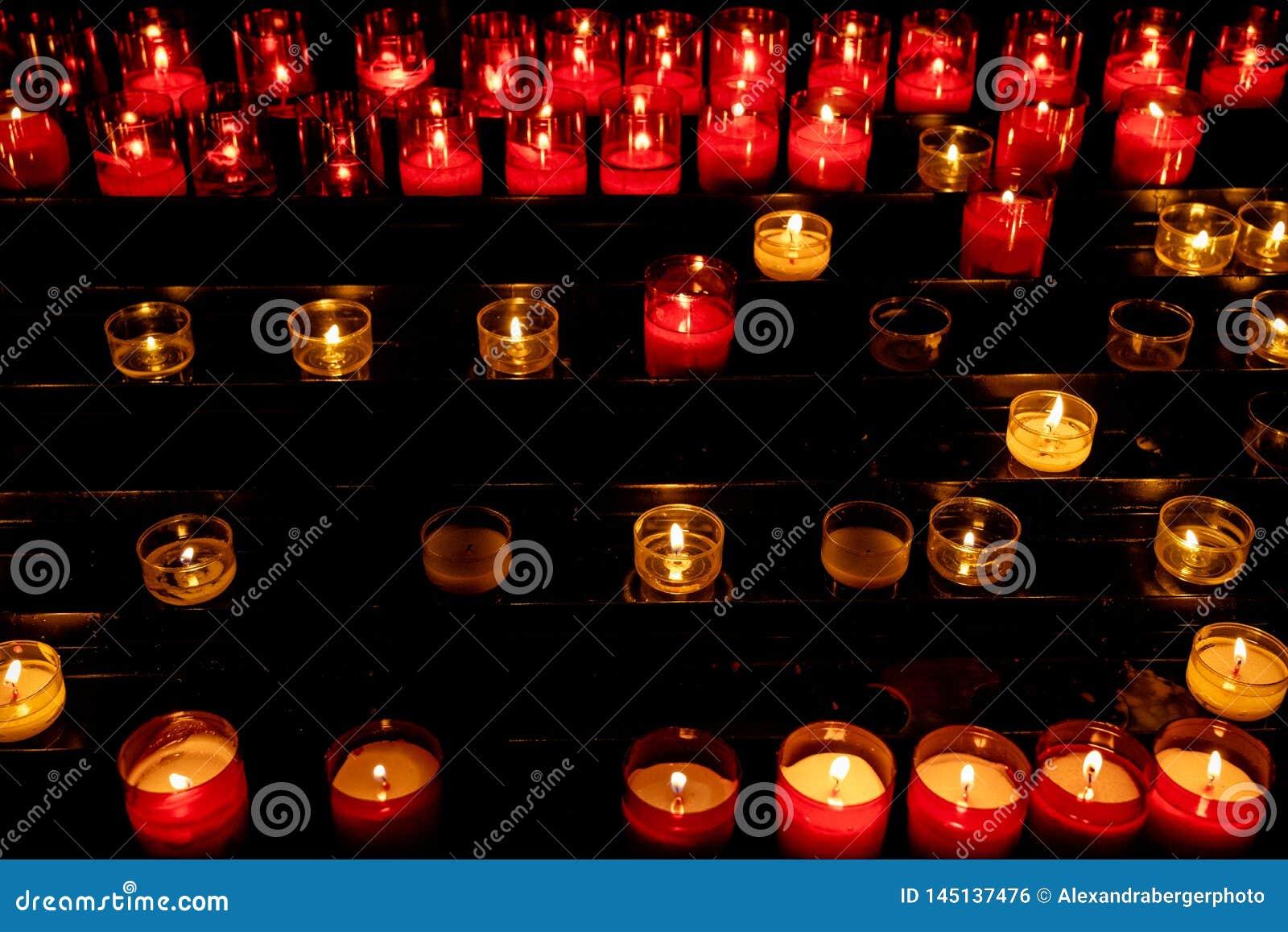 白色和红灯蜡烛在教会里在黑暗中