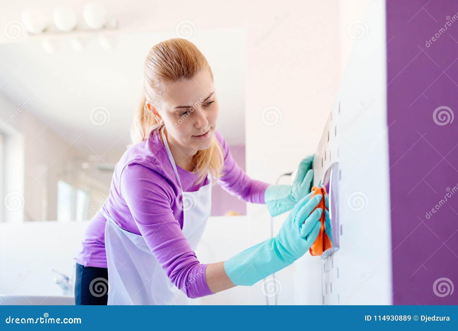 白色围裙清洁洗手间按钮的妇女