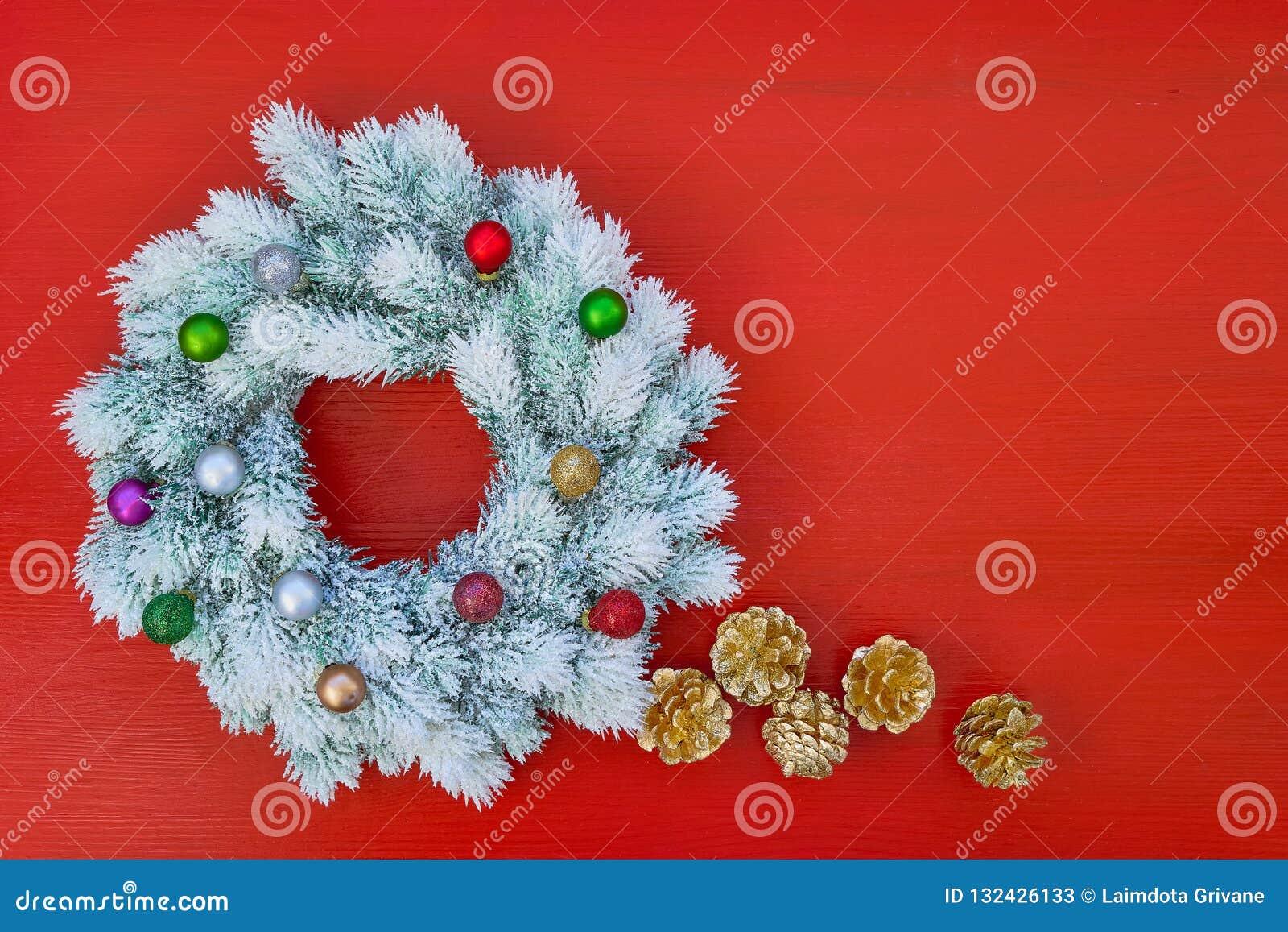 白色圣诞节快乐缠绕与在红色backgroun的圣诞节装饰品