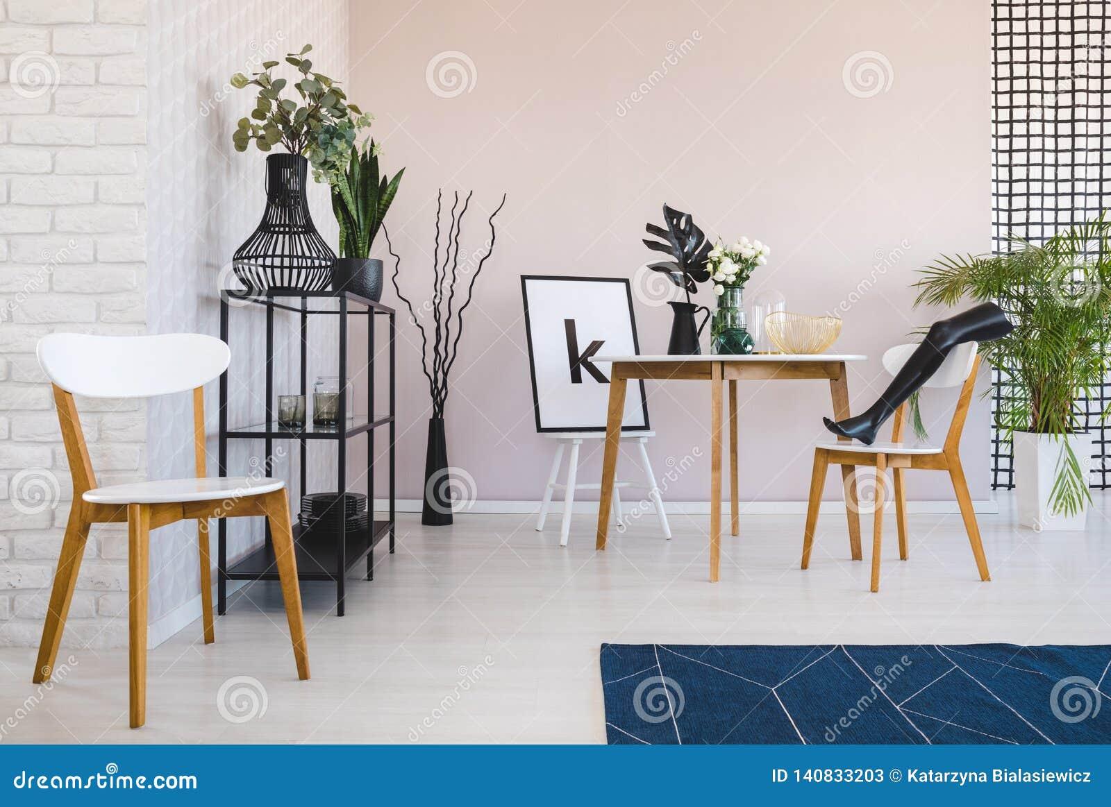 白色木椅子和蓝色地毯在餐厅内部与植物在桌旁边 实际照片