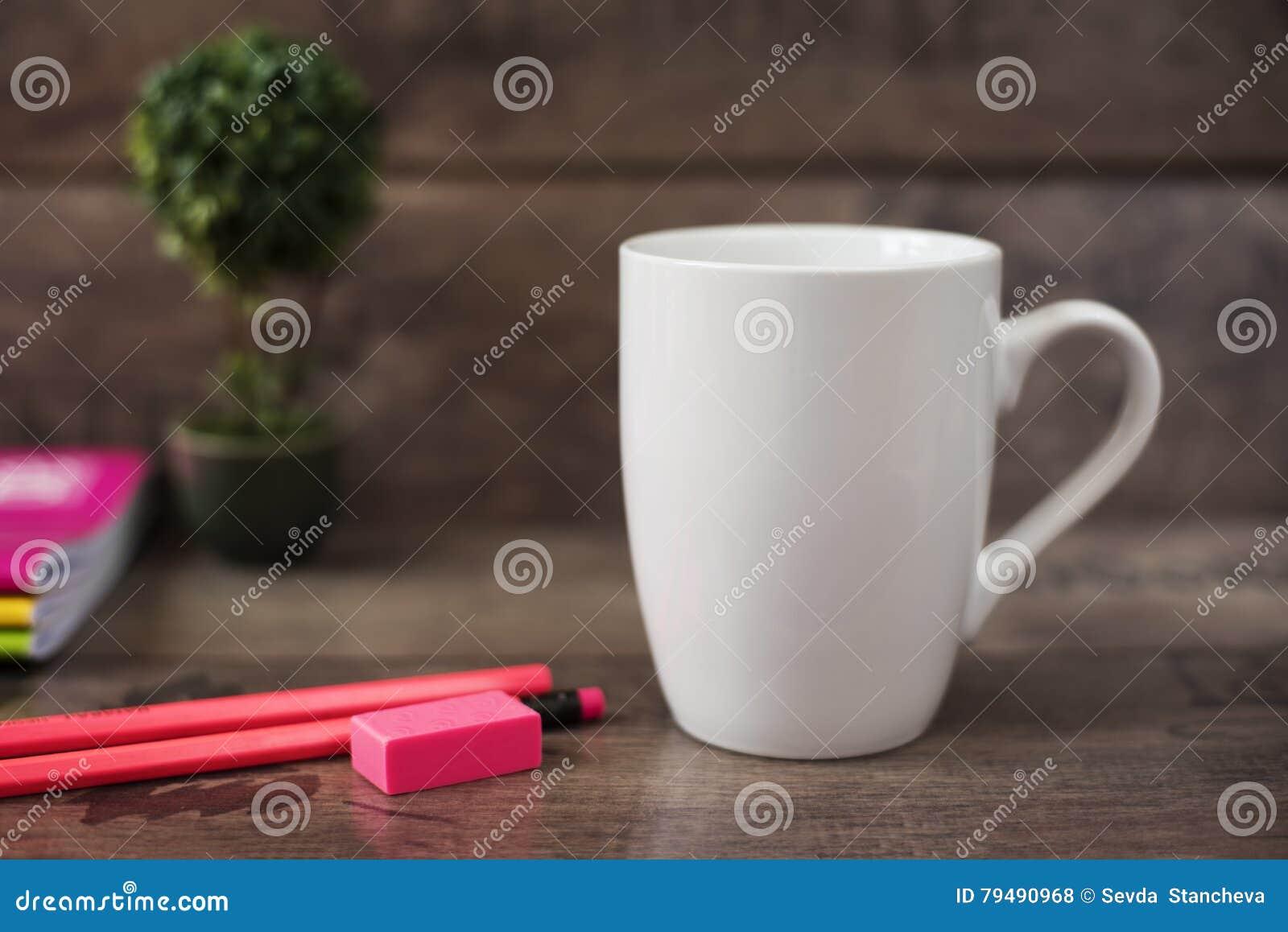 白色杯子大模型 空白杯子 与明亮的氖的咖啡杯大模型上色铅笔和笔记本 后边盆的植物盆景