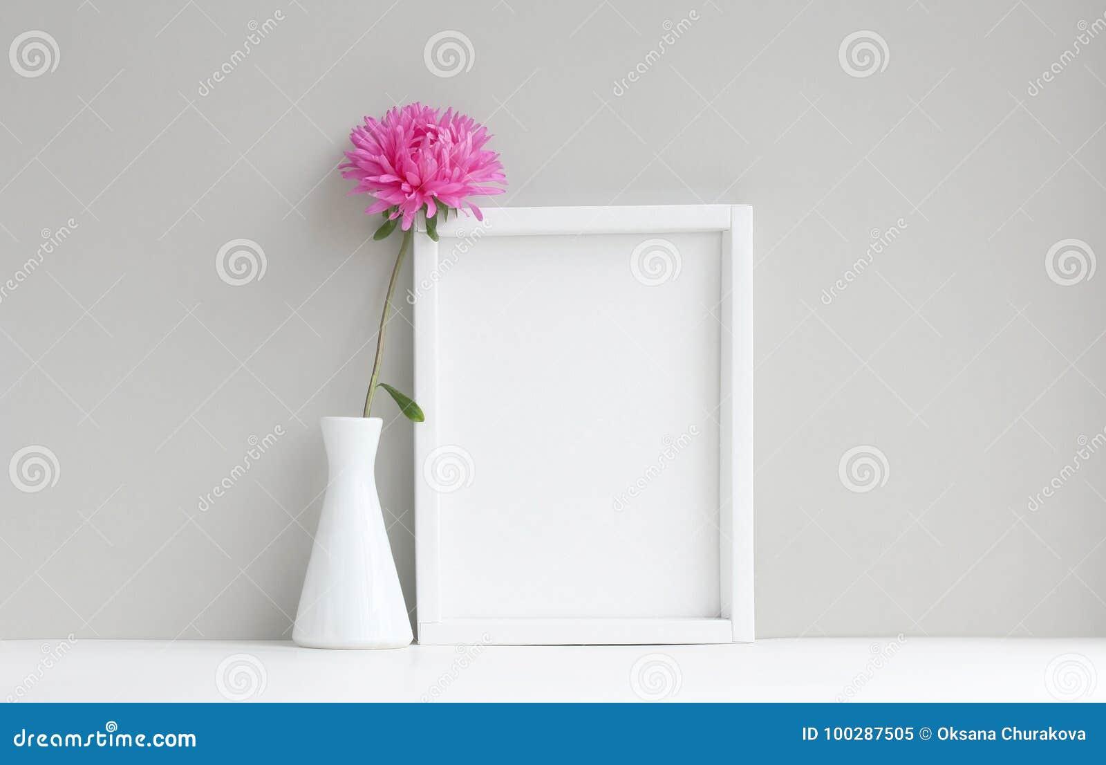 白色框架,空的大模型,在有桃红色翠菊的花瓶旁边